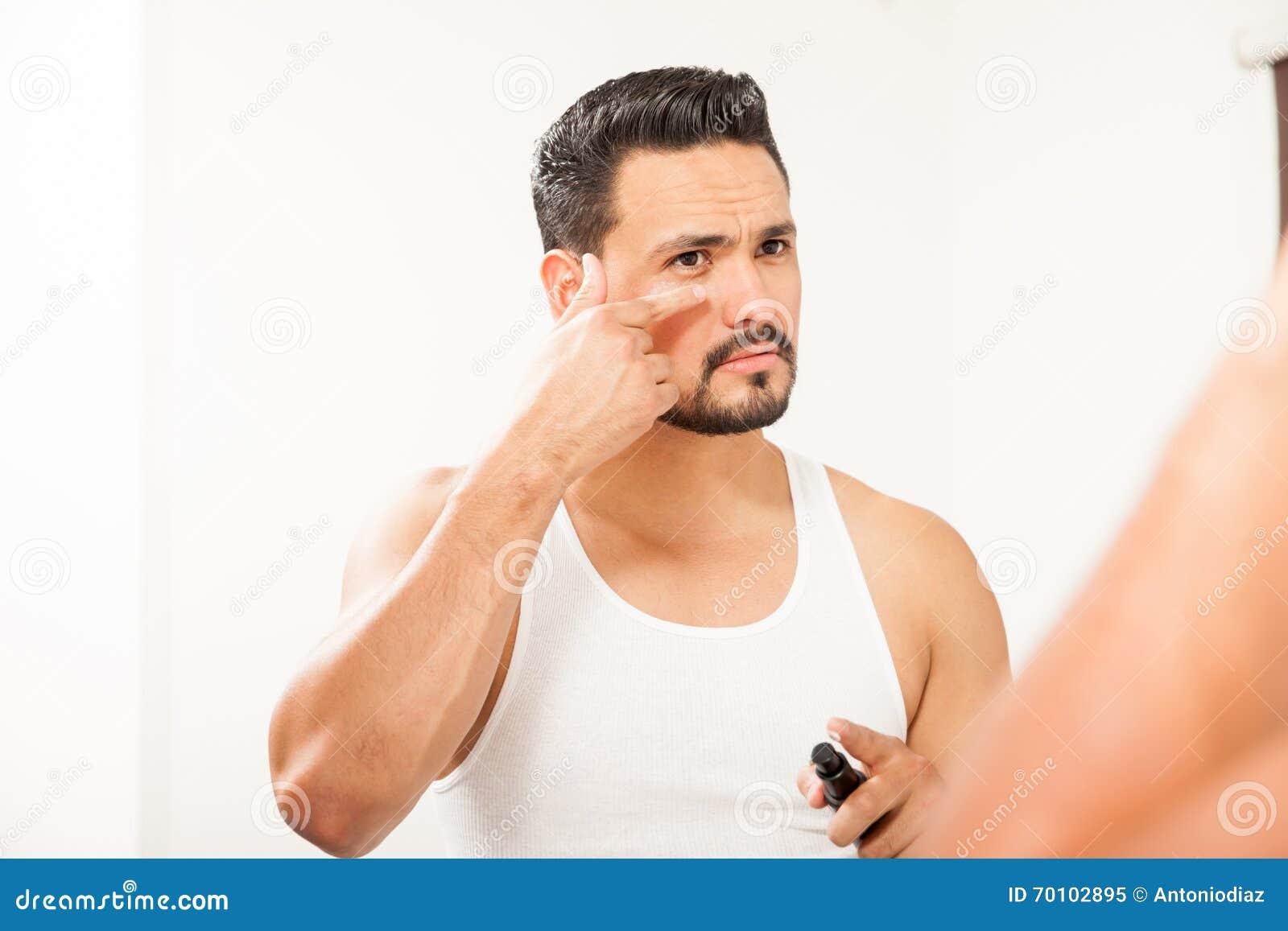 Hispanic Man Using An Under Eye Cream Stock Image - Image of