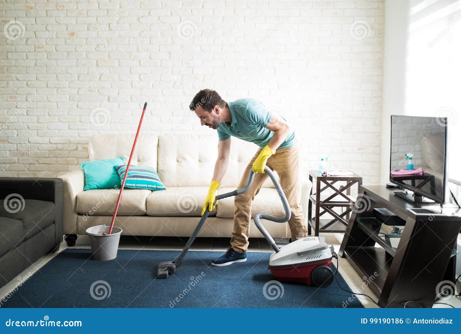 Hispanic man vacuuming the living room