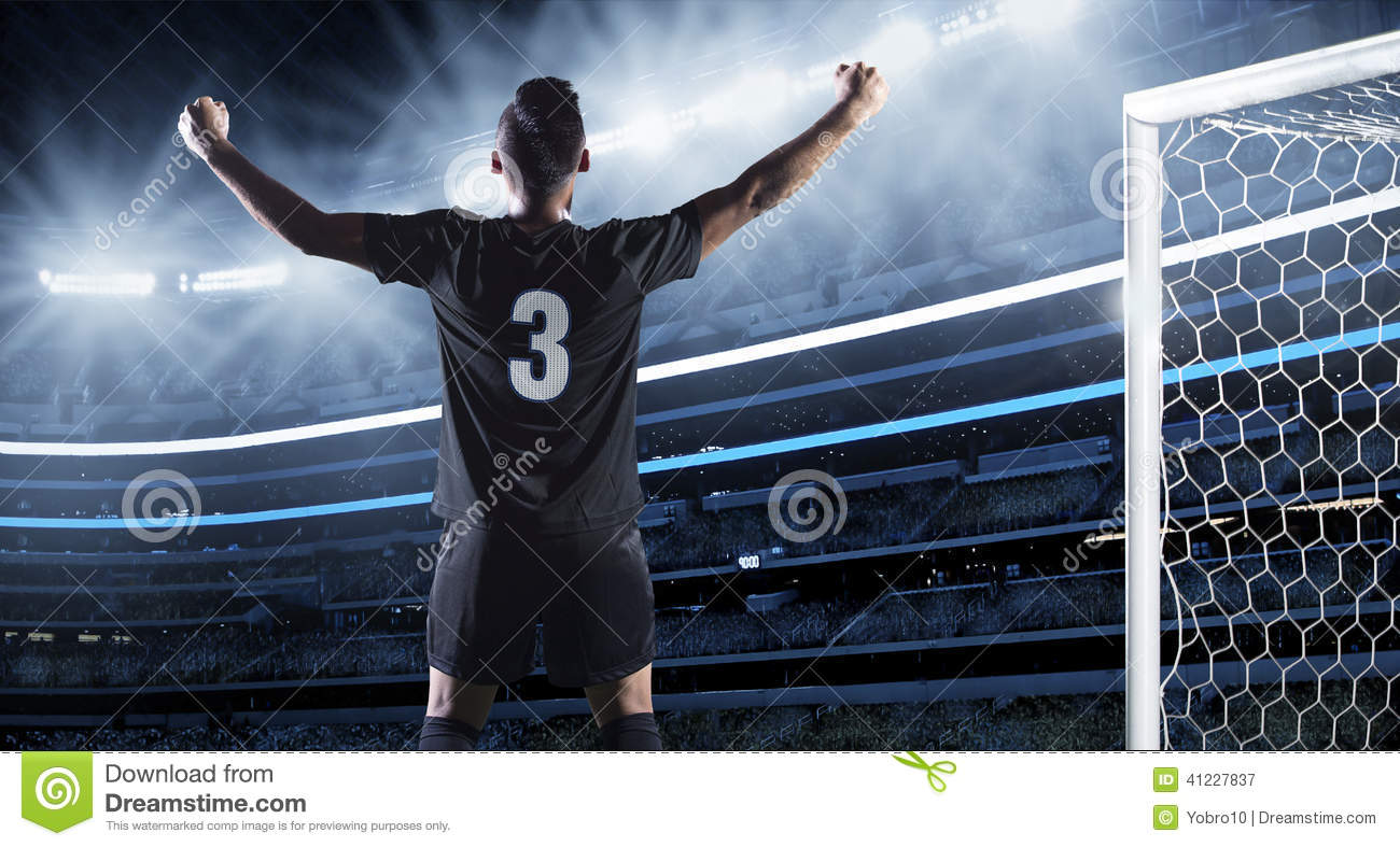 soccer player raising his arms in celebration of scoring a goal ...