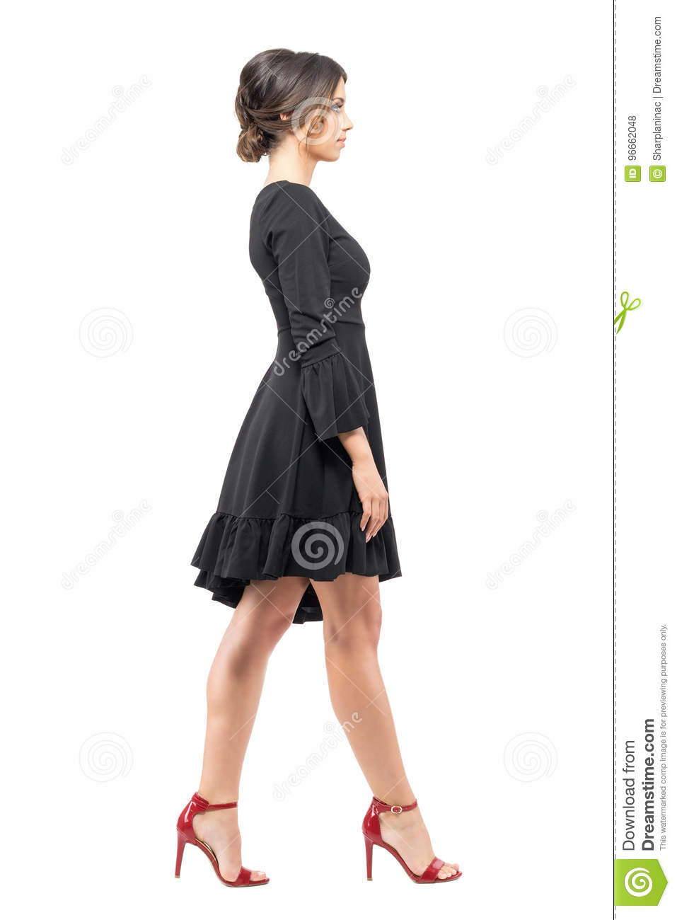 Hispanic woman in black dress and red high heels sandals walking looking ahead side view
