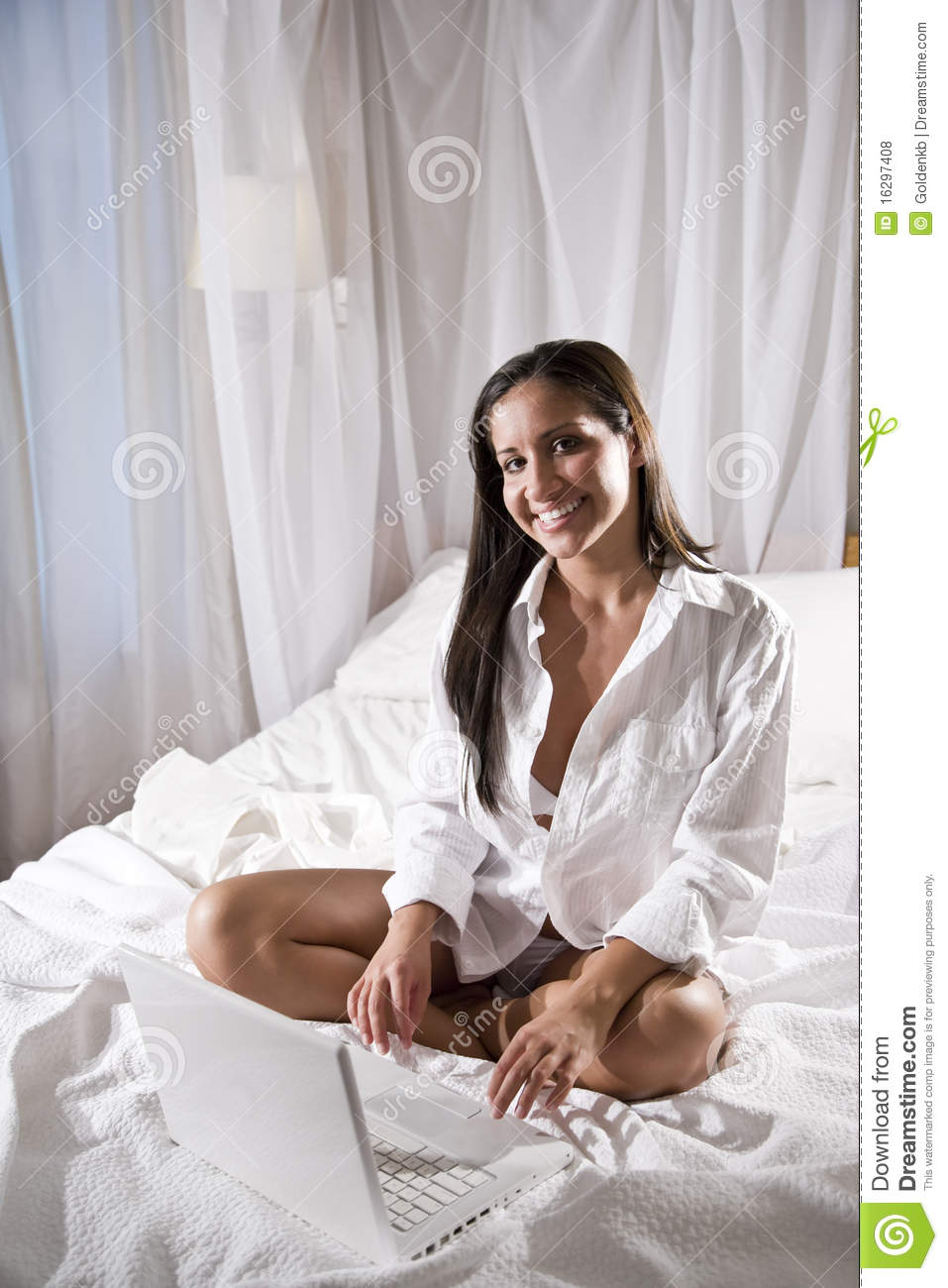 Hispanic Woman Sitting On Bed Using Laptop Royalty Free