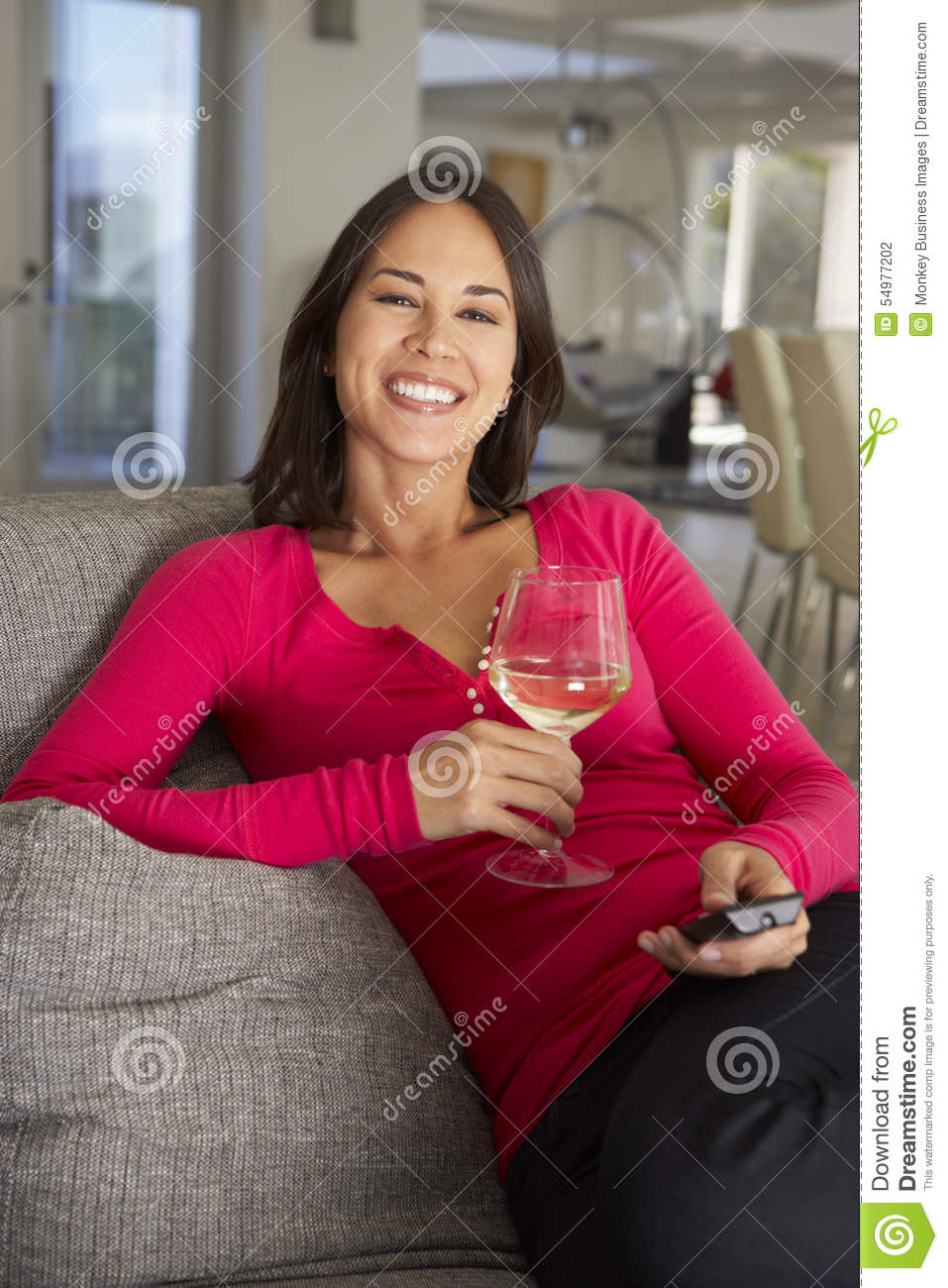 Hispanic Woman On Sofa Watching TV Drinking Wine