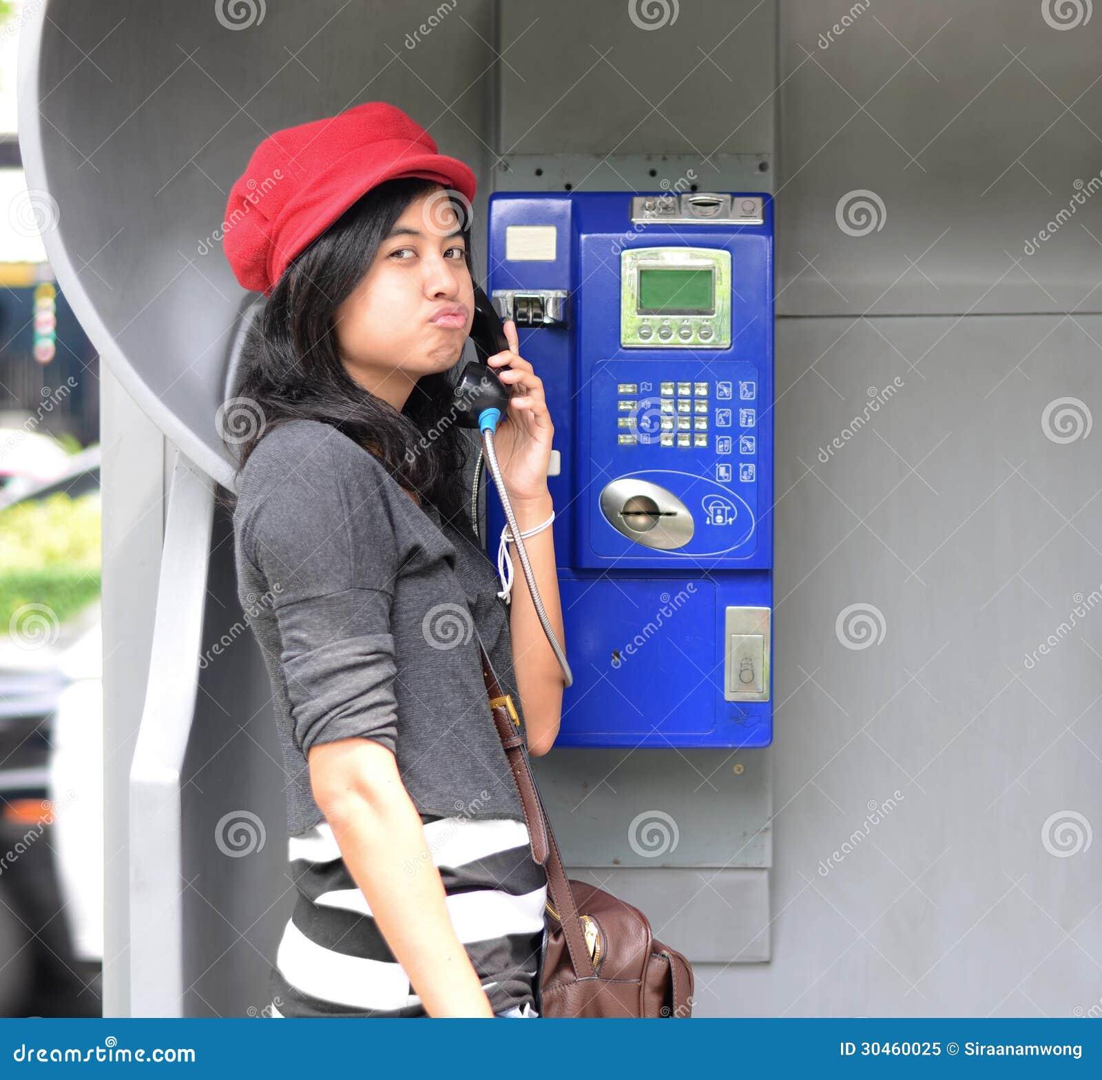 Hispanic woman talking in a public phone