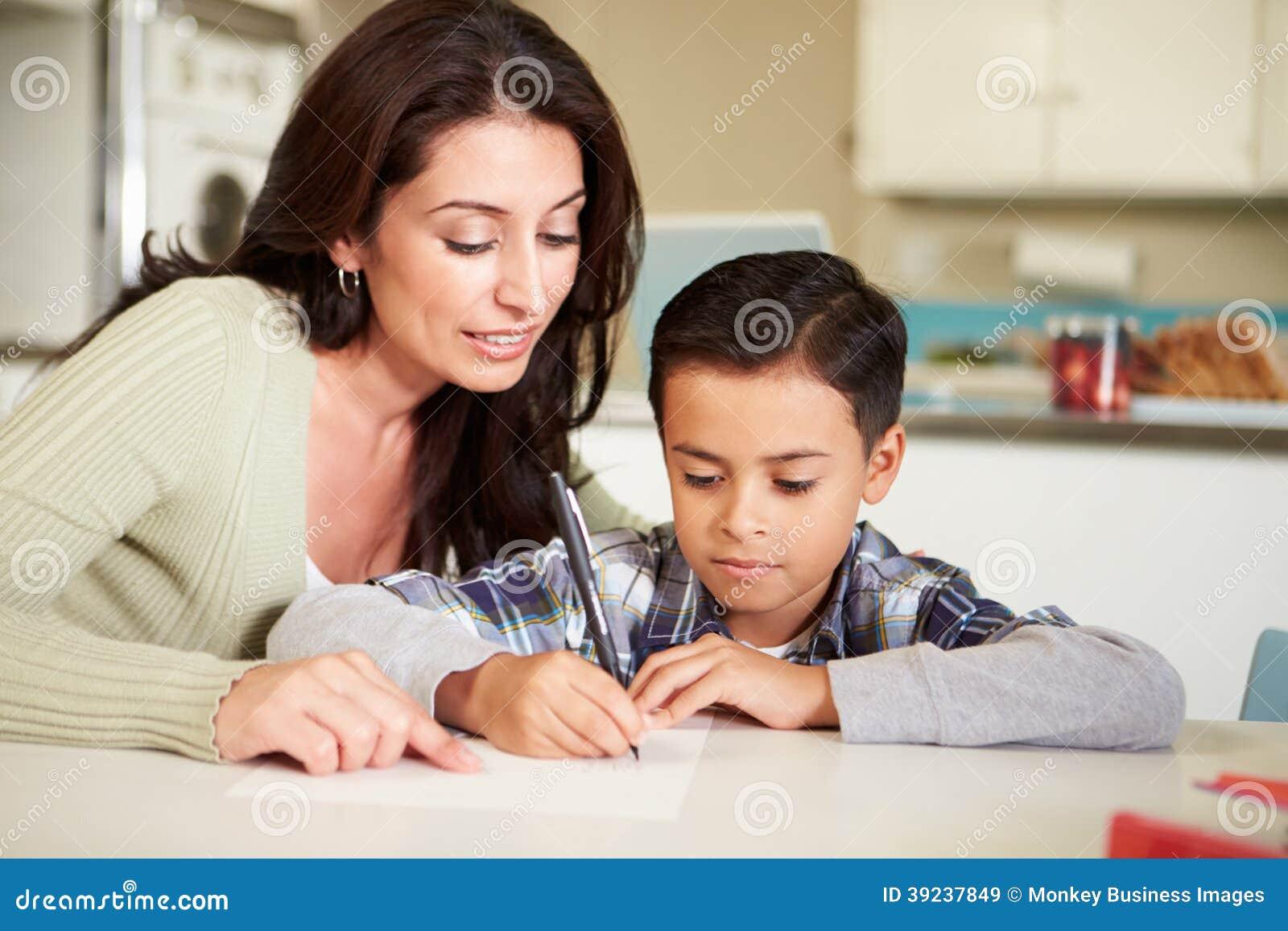 Hispanische Mutter-helfender Sohn mit Hausarbeit bei Tisch