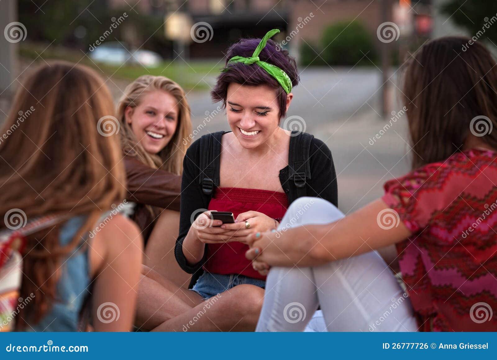 Hispanisches jugendlich mit Freunden und Telefon