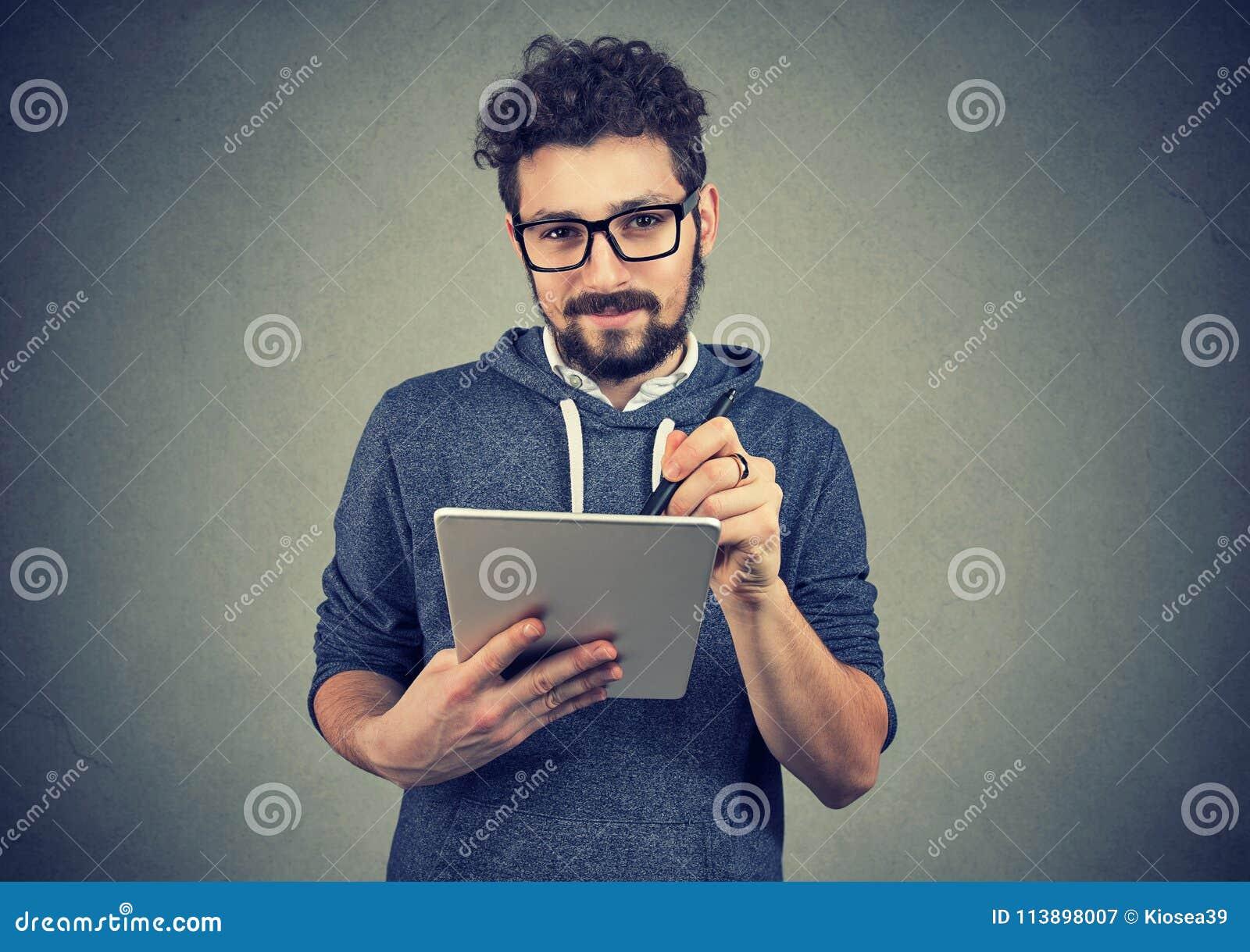 Hispter mężczyzna trzyma pastylki pióro i komputer patrzeje kamerę w szkłach