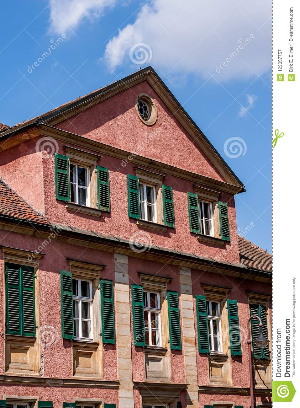historic building with lattice windows and green shutters editorial