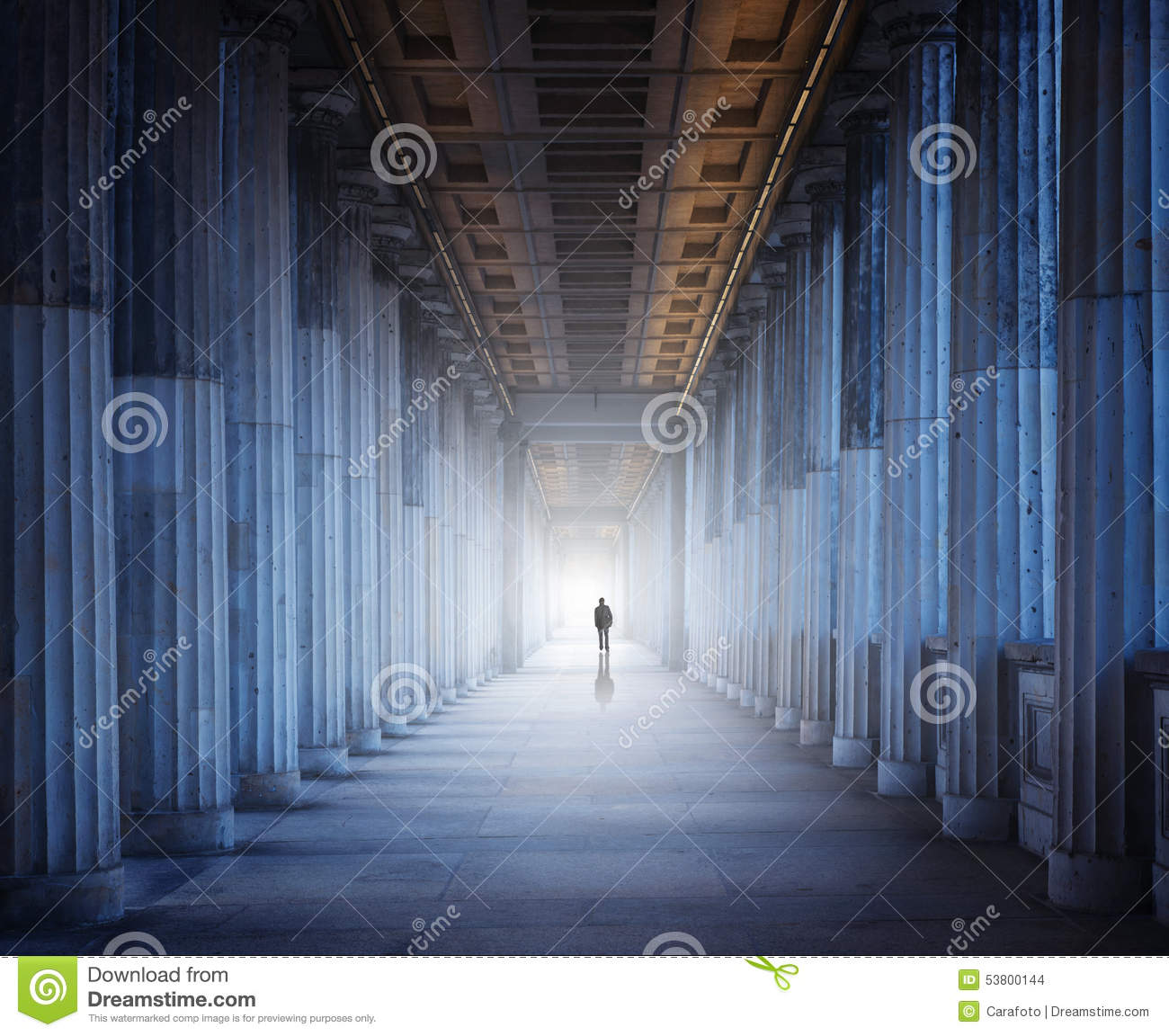 A historical building and a man walking into the light