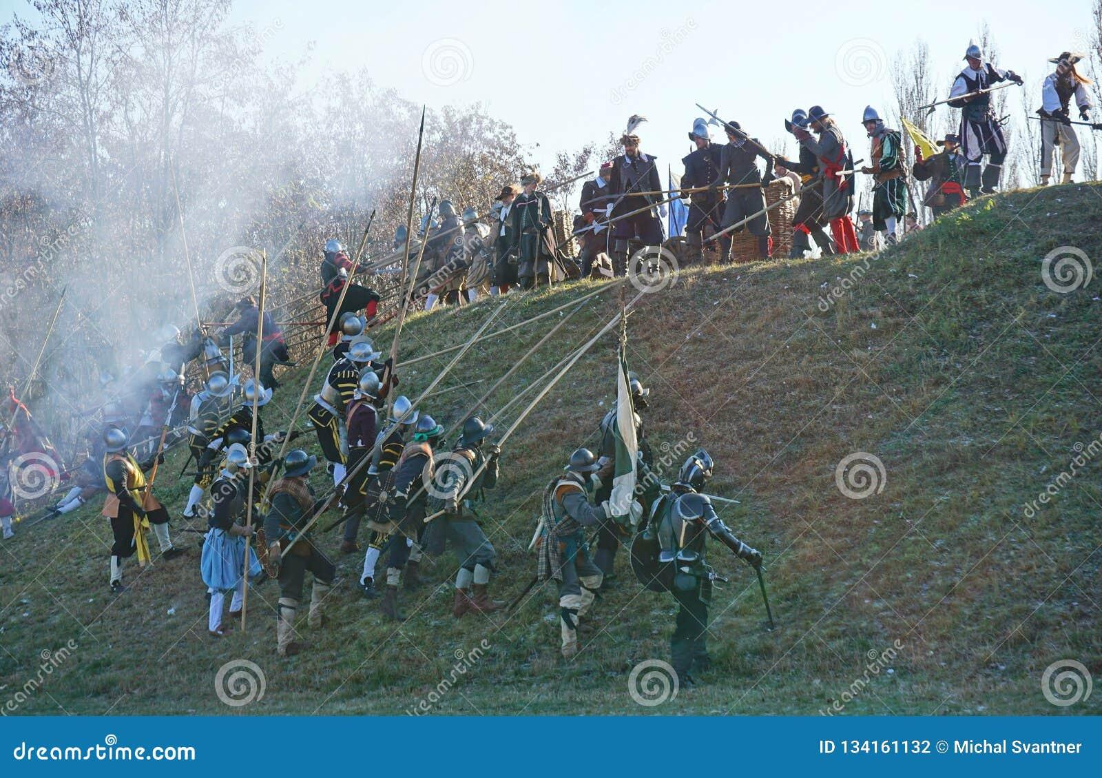 Historische Kampfrekonstruktion - Angreifer, die oben einen Hügel gegen Verteidiger laufen lassen