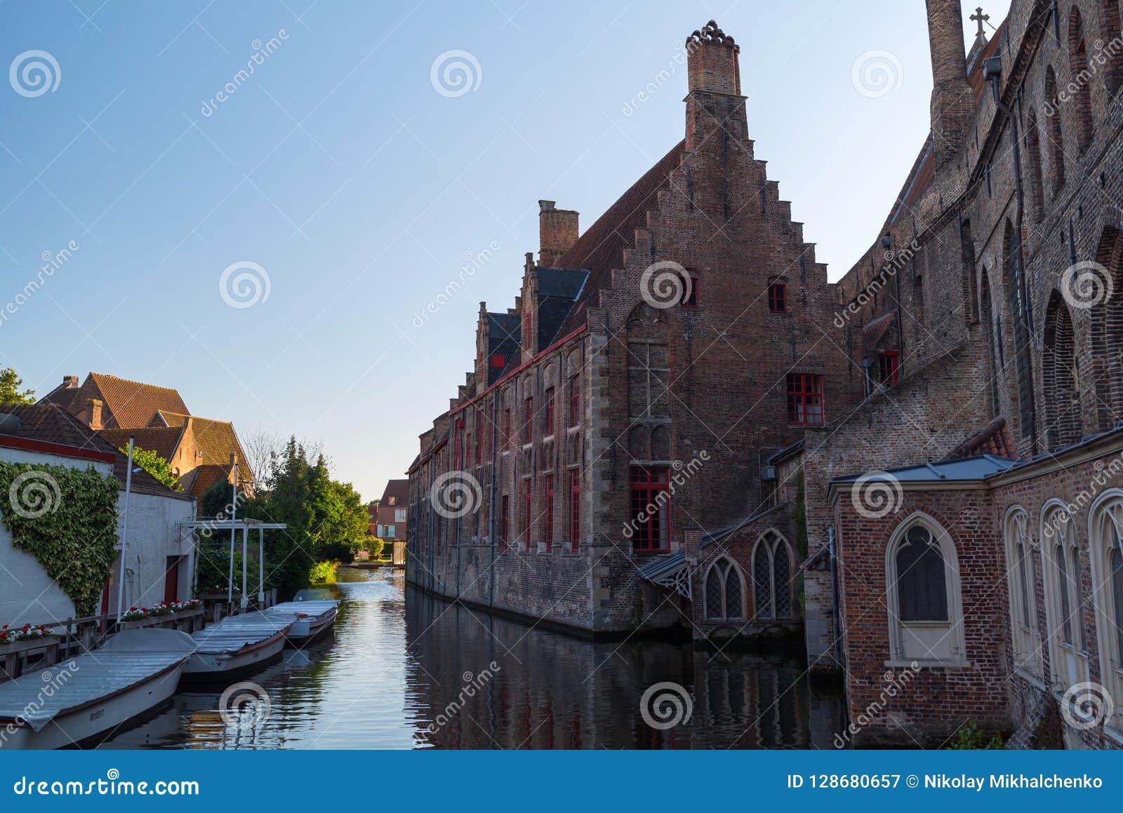 Historiska medeltida byggnader med den härliga kanalen i den gamla staden av Bruges Brugge