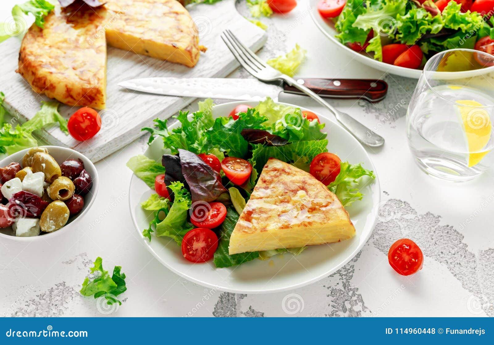 Hiszpański tortilla, omelette z grulą, cebula, warzywa, pomidory, oliwki i ziele w białym talerzu, śniadanie