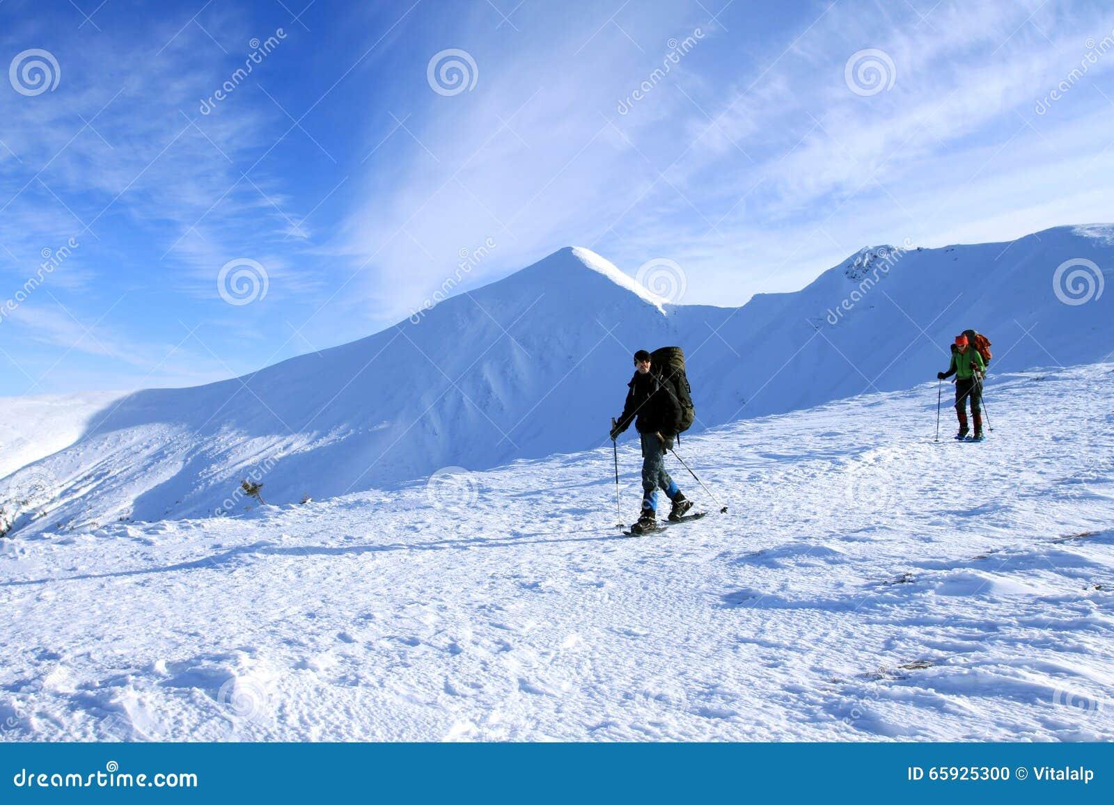 Hiver augmentant dans les montagnes avec un sac à dos et une tente