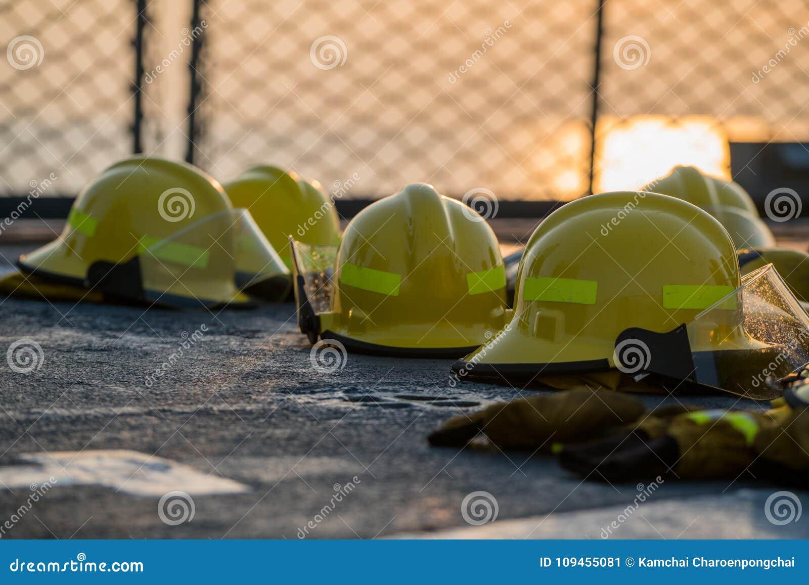 Hjälmar för brandstridighet torkar på däcket för marinskeppet efter bruk Säkerhetsnät har sett som en bakgrund orange himmel mell