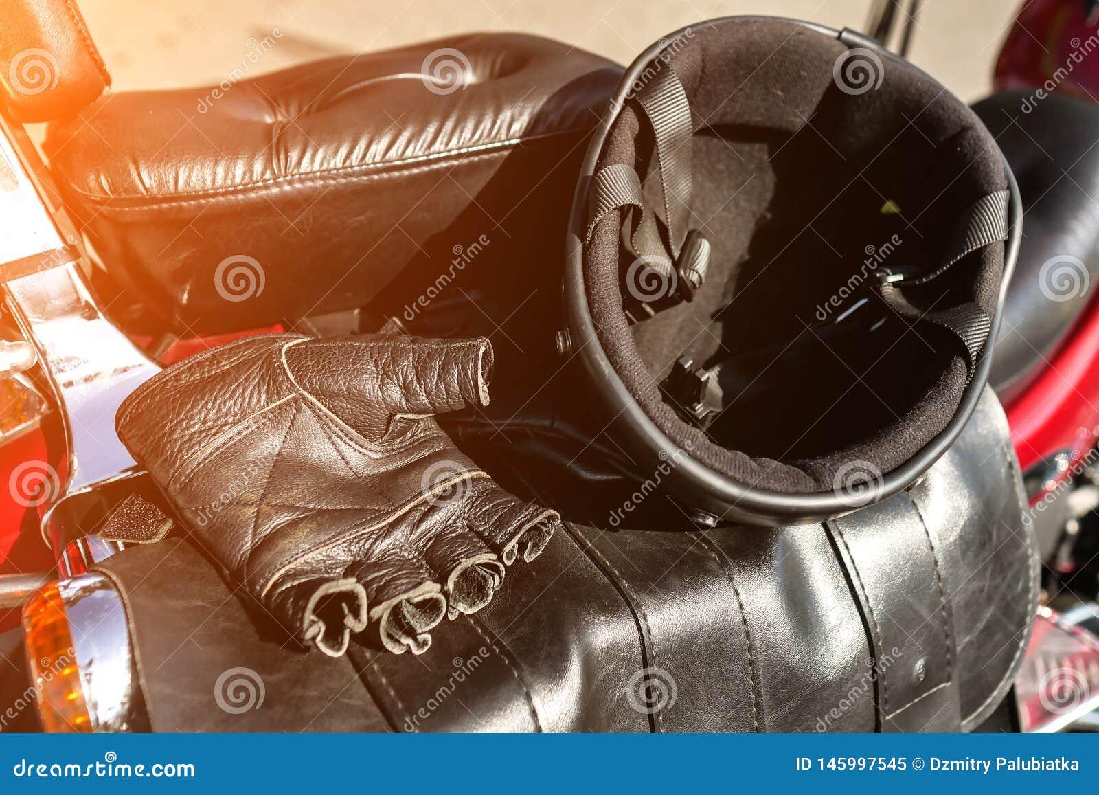 Hjälmen och handskar är på platsen av motorcykeln