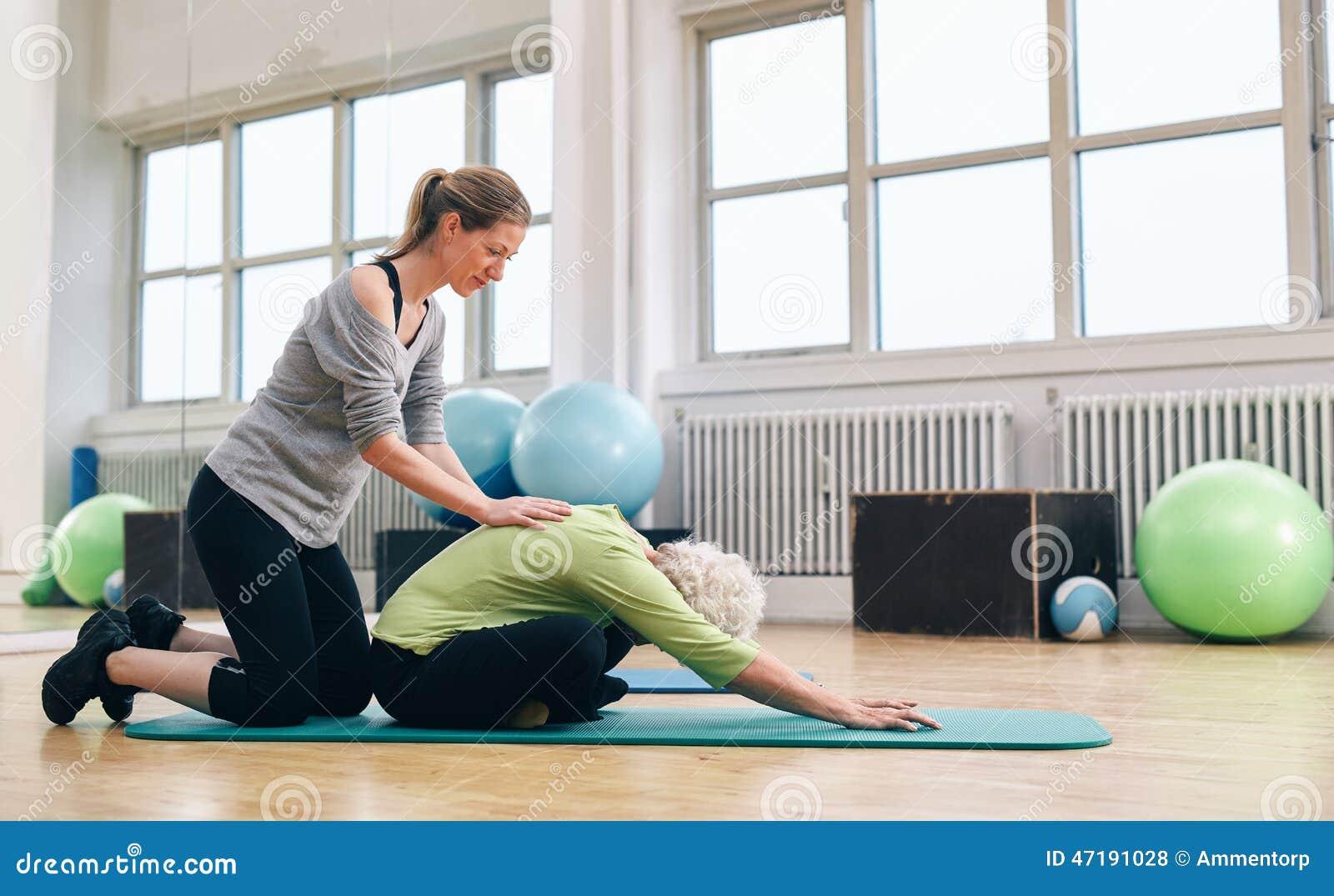 Hjälpande äldre kvinna för fysisk instruktör som gör yoga