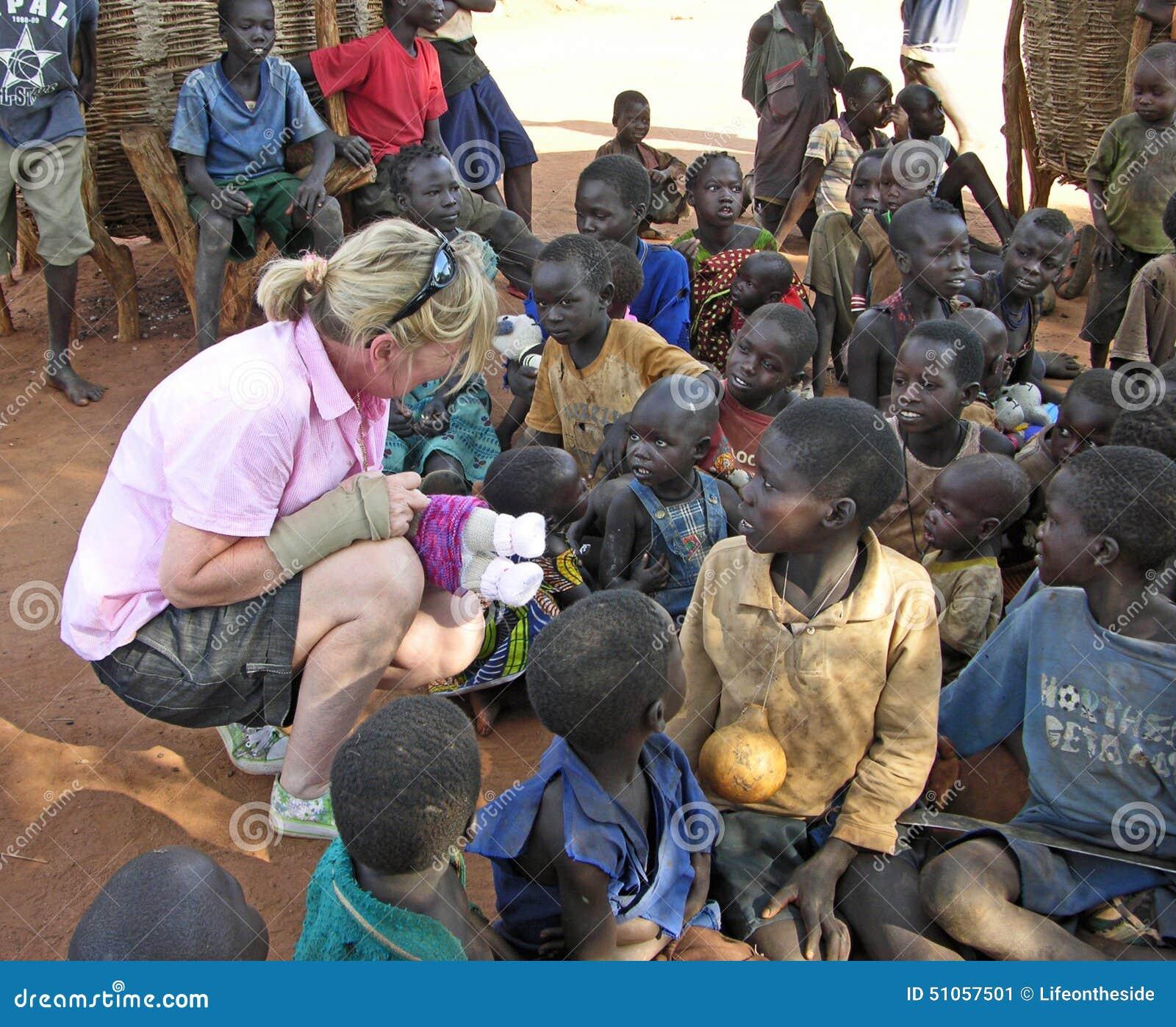 Hjälparbetaren kommer med hopp till att le afrikanska barn i byn Uganda