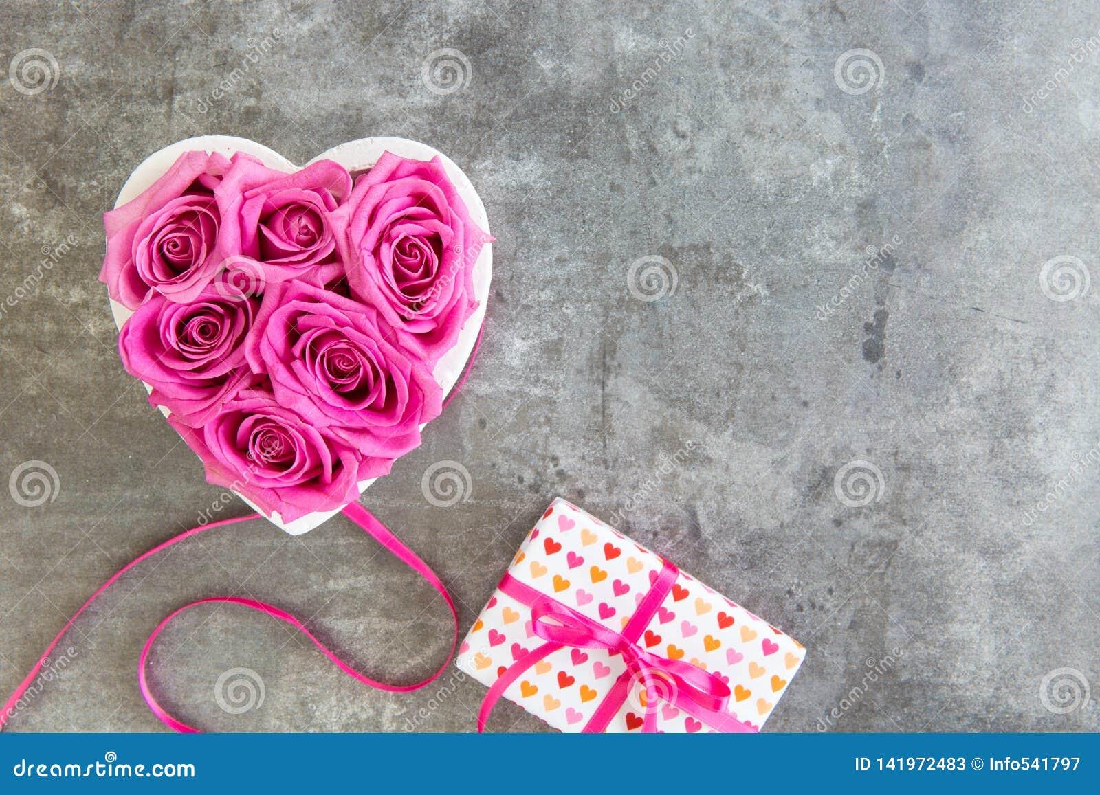 Hjärta av rosor i rosa färg- och gåvaask med pilbågen, mors dag