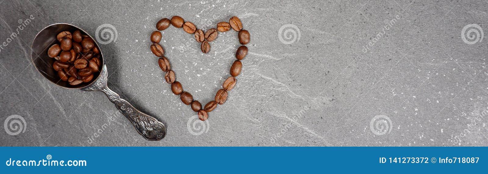 Hjärta för kaffebönor från bönor för mässahandel med skeden på grå kökworktopbakgrund
