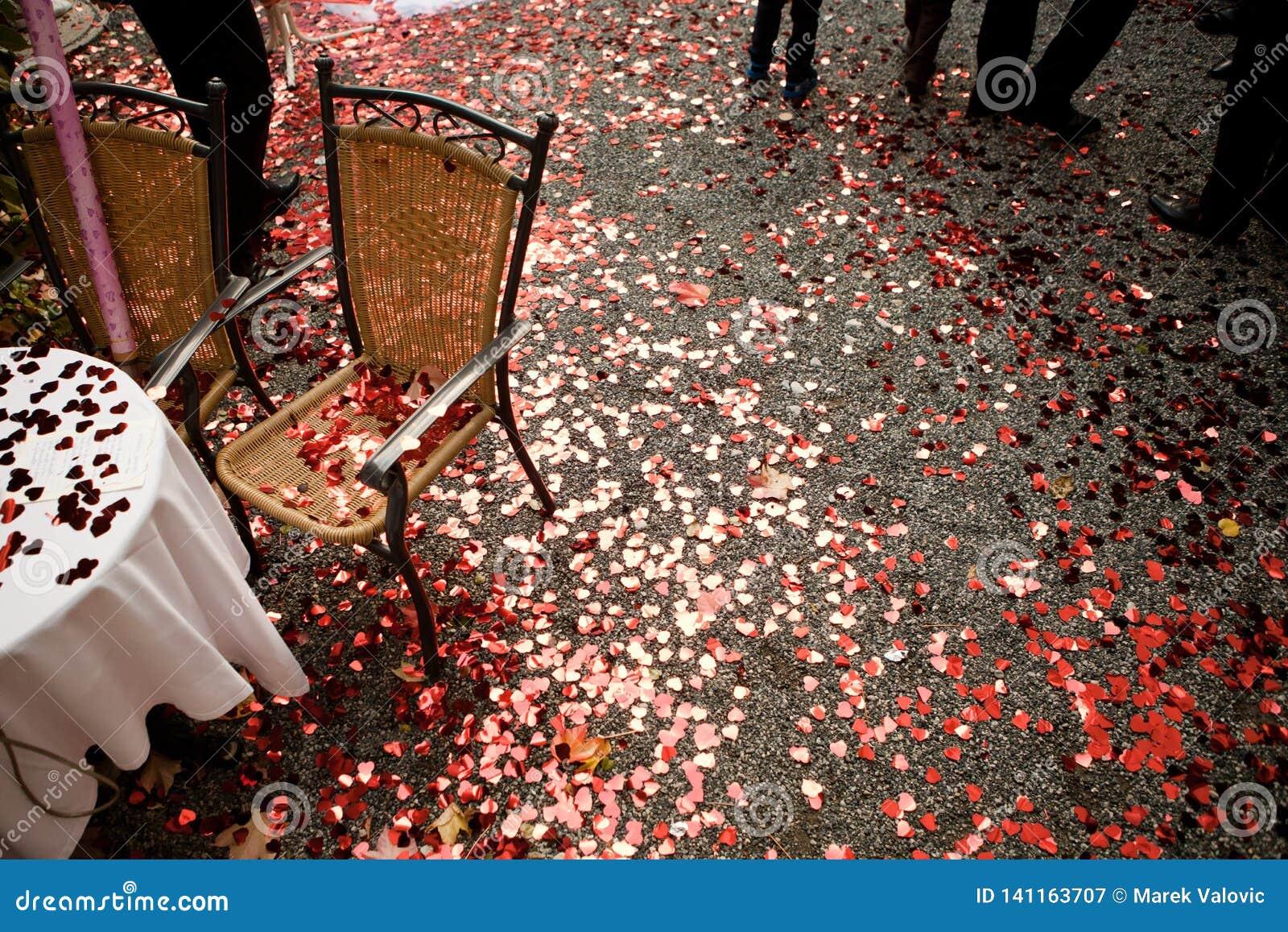 Hjärta formade röda konfettier på jordningen