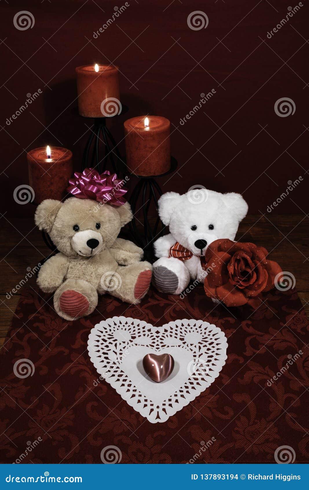 Hjärta shapped dollie och gemstonen, tre röda stearinljus i metallholoders och den röda rosen, två nallebjörnar på trätabellen
