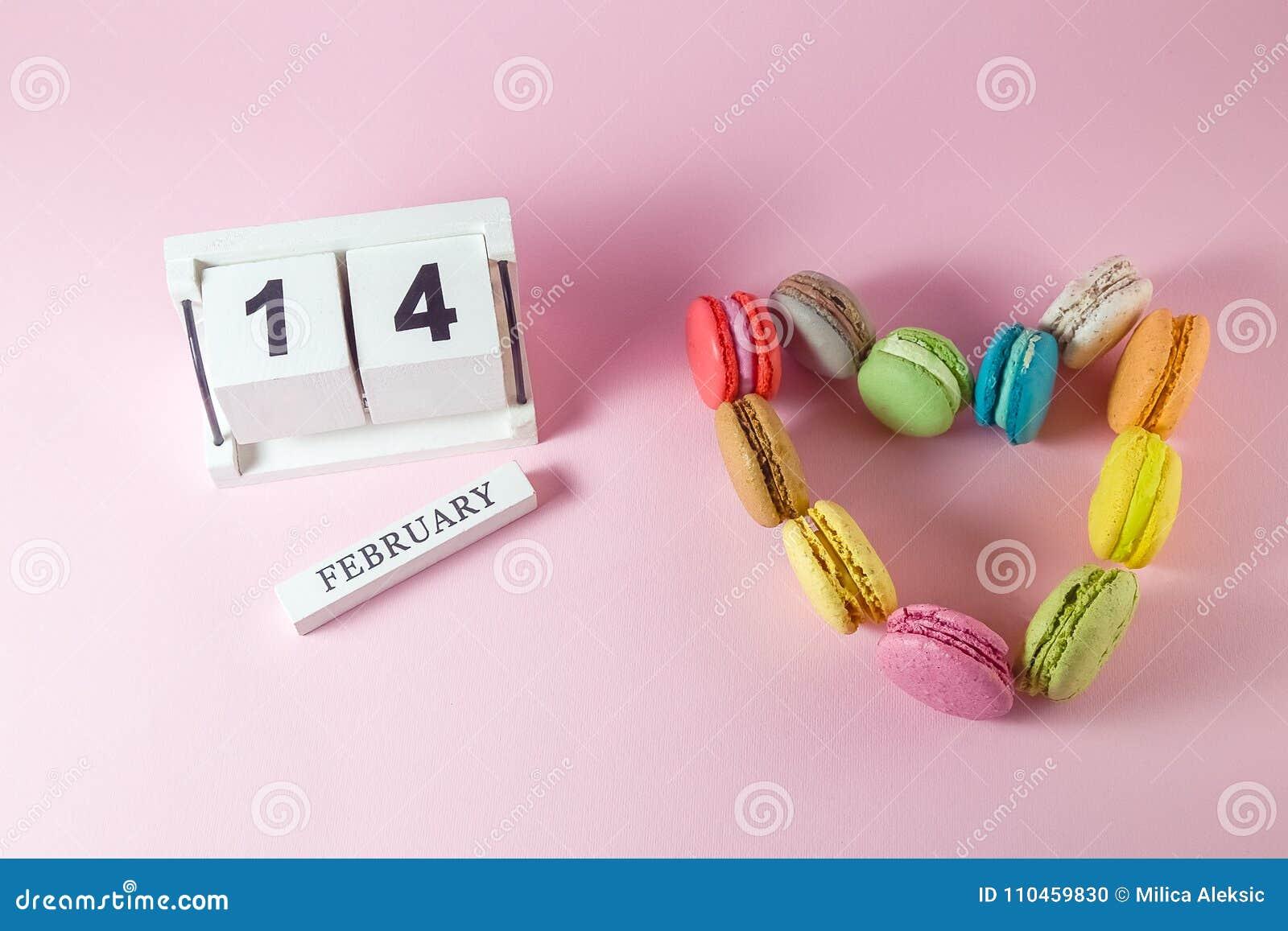 Hjärta som göras av färgrika macarons och träkalender