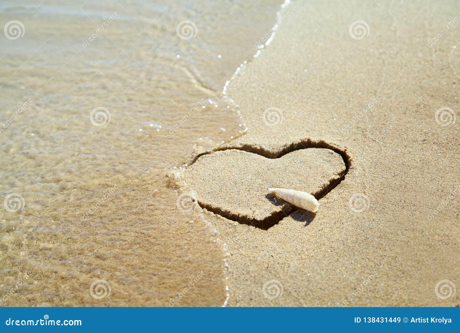 Hjärta som göras av sand på stranden man för begreppskyssförälskelse till kvinnan