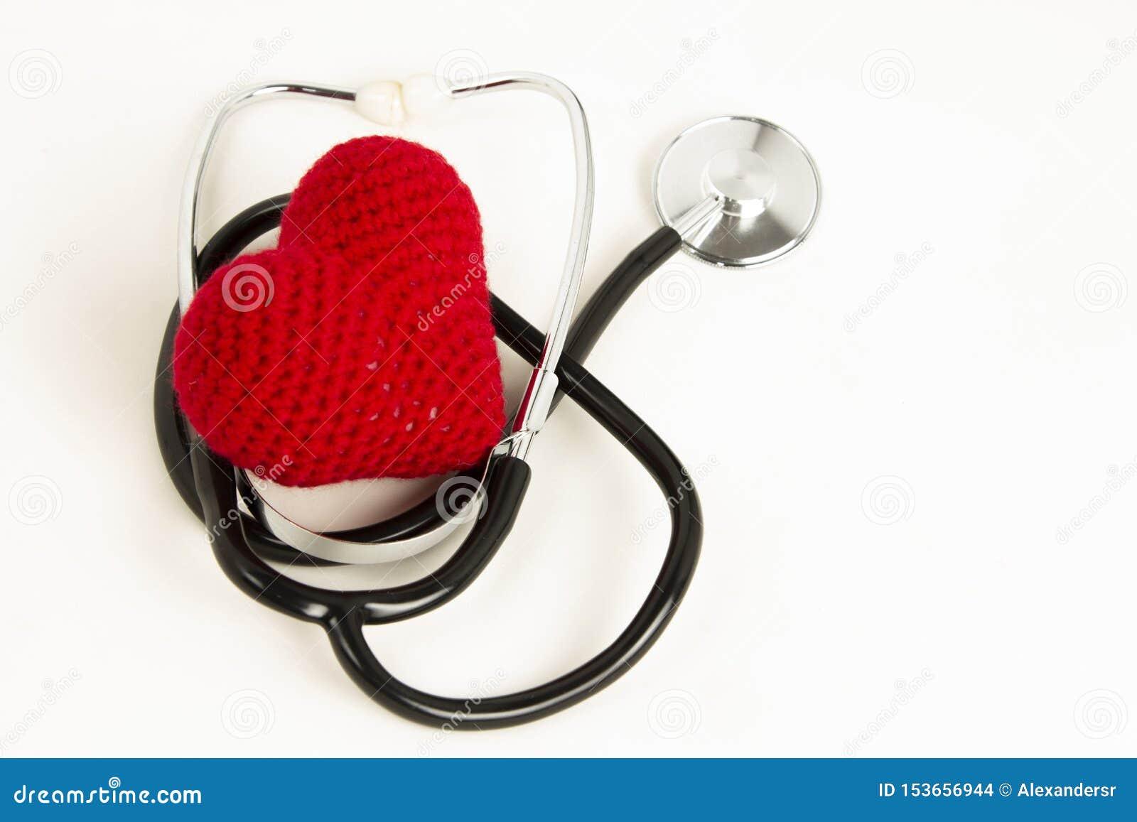 Hjärtahälsa och förhindrandebegrepp Stetoskop och röd hjärta av virkning på vit isolerad bakgrund med utrymme för text