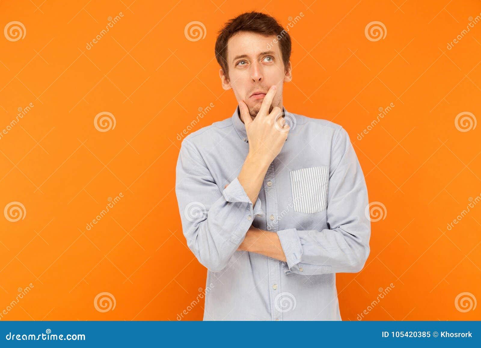 Hmm, pensamiento de la necesidad del ` m de i Hombre adulto joven que mira para arriba, sosteniendo la barbilla