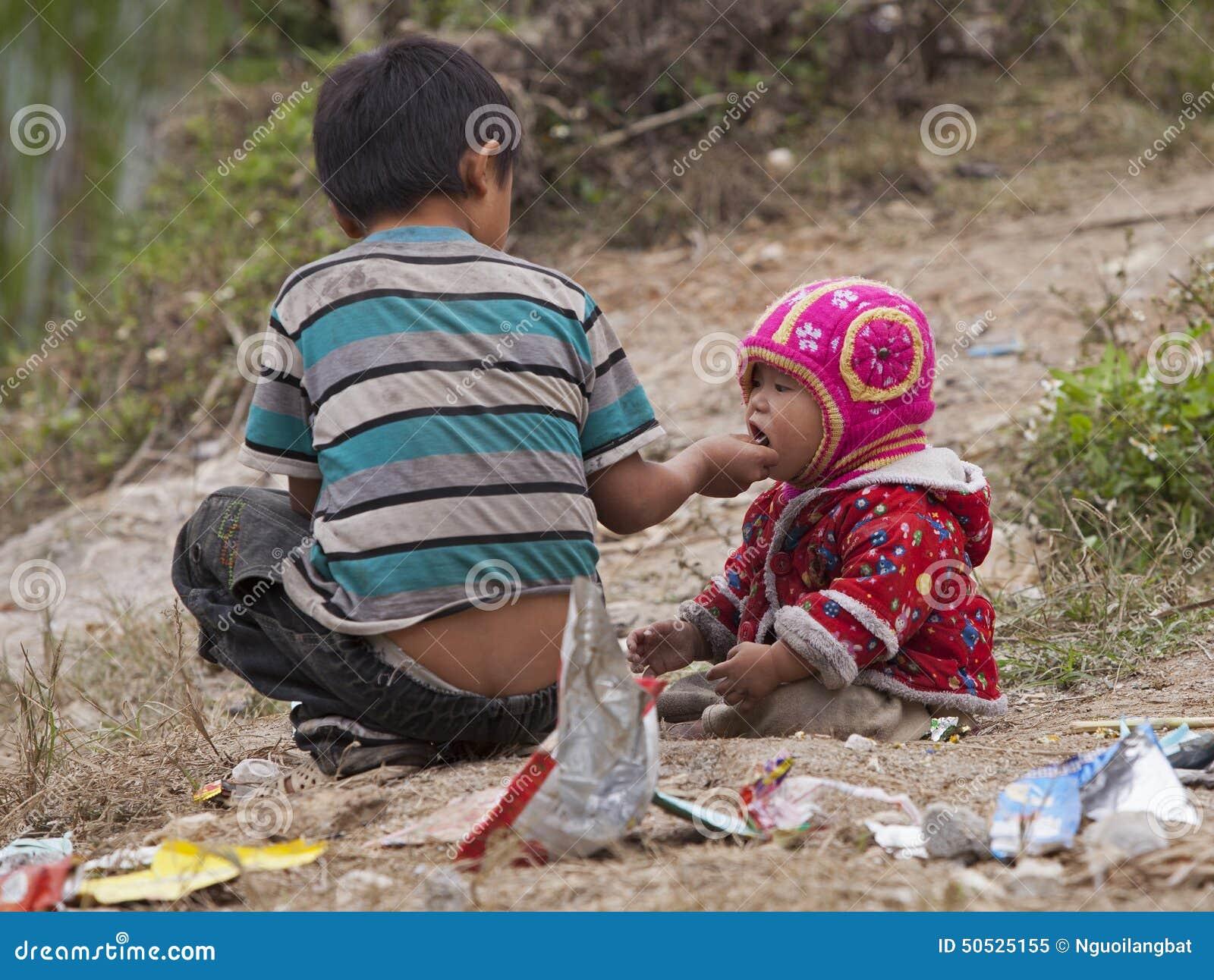 Hmong barn som äter godisen på den smutsiga jordningen i Dong Van den steniga platån