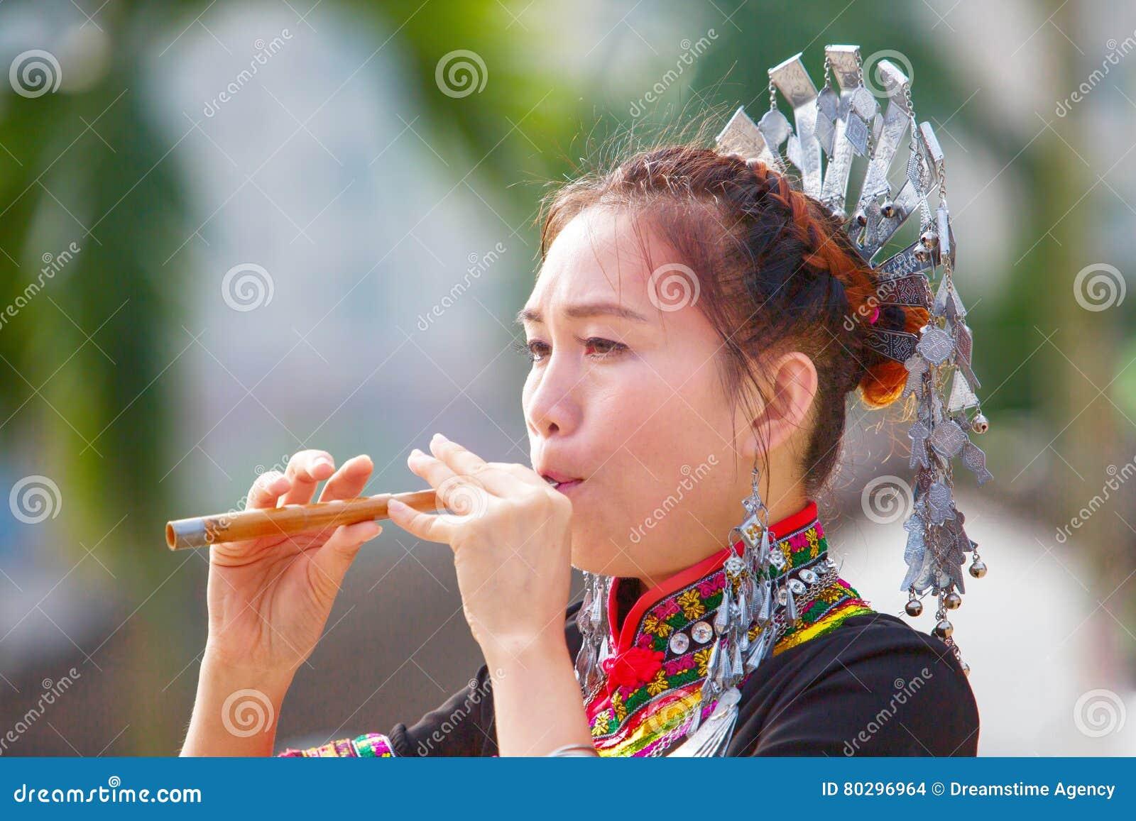 Hmong kobiety na ich tradycyjnych sukniach bawić się ich swój muzycznego instrument