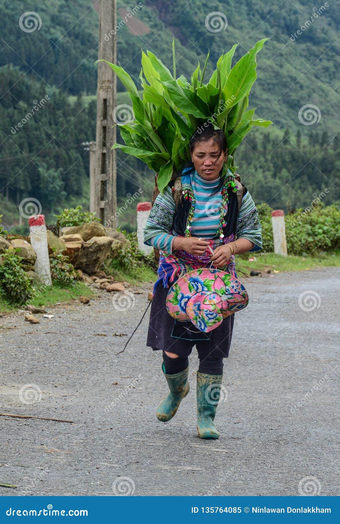 Hmong kvinna som går på bergvägen