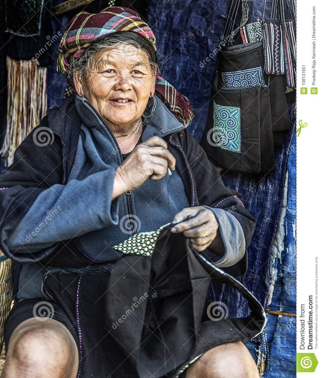 Hmong tribal old woman hand tailoring bags in her shop, Sapa, Vietnam