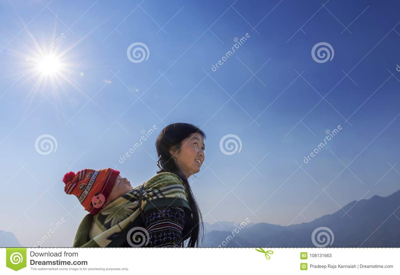 Hmong tribe woman carrying her child at her back in Sapa, Vietnam