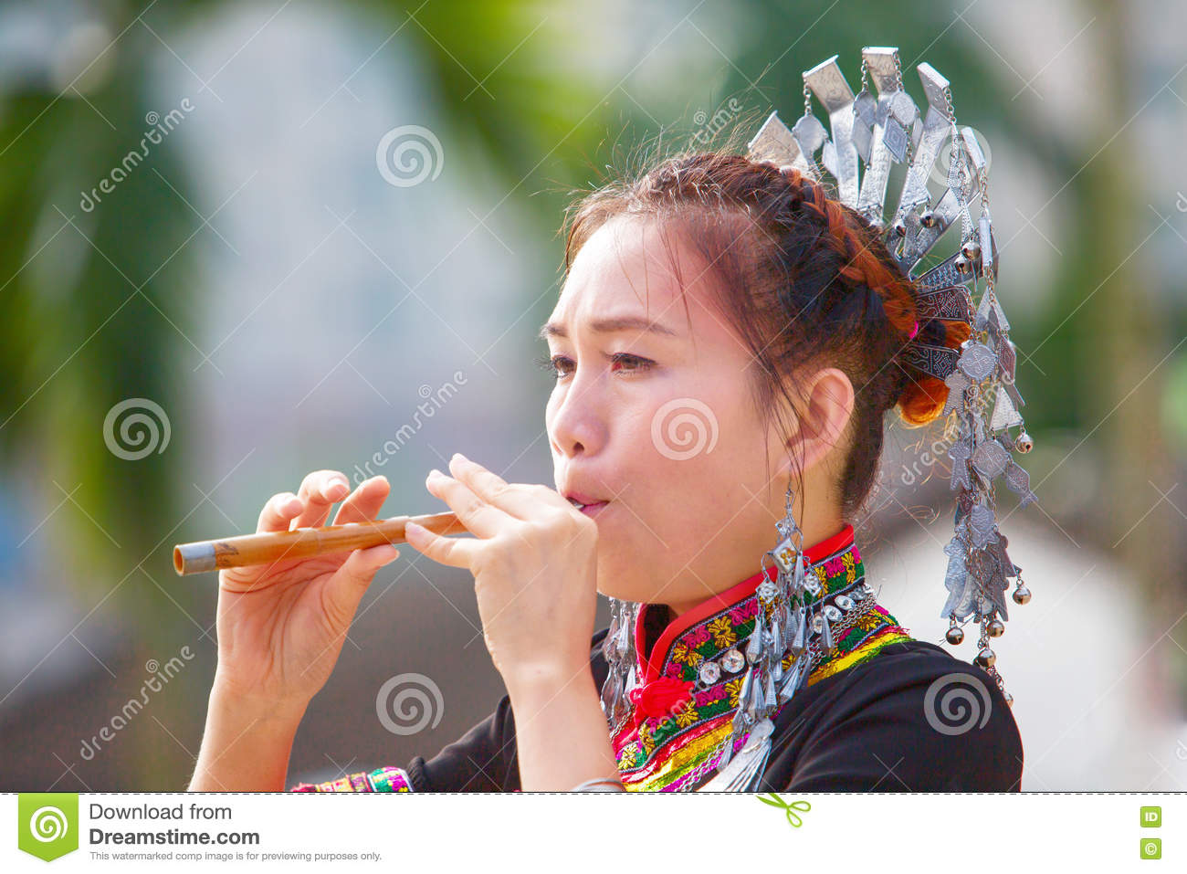 The Hmong women on their traditional dresses is playing their own music instrument