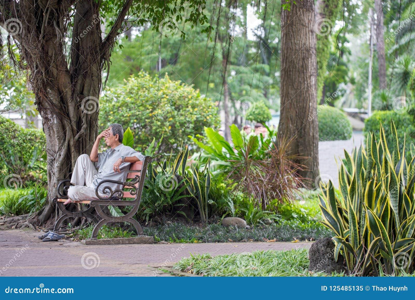 Ho Chi Minh miasto Wietnam, Wrzesień, - 1, 2018: niezdefiniowany mężczyzna obsiadanie przy kątem parkowy główkowanie o coś