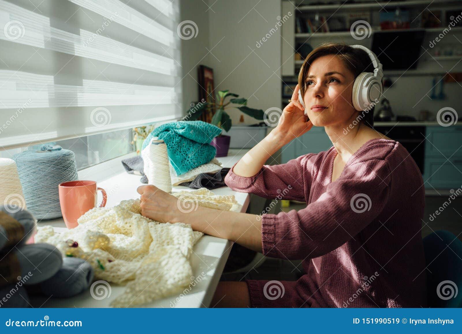 Hobby, stemmings en vrije tijdsconcept Vrouw het ontspannen met hoofdtelefoons terwijl de breiende tedere kleding met in zonnige