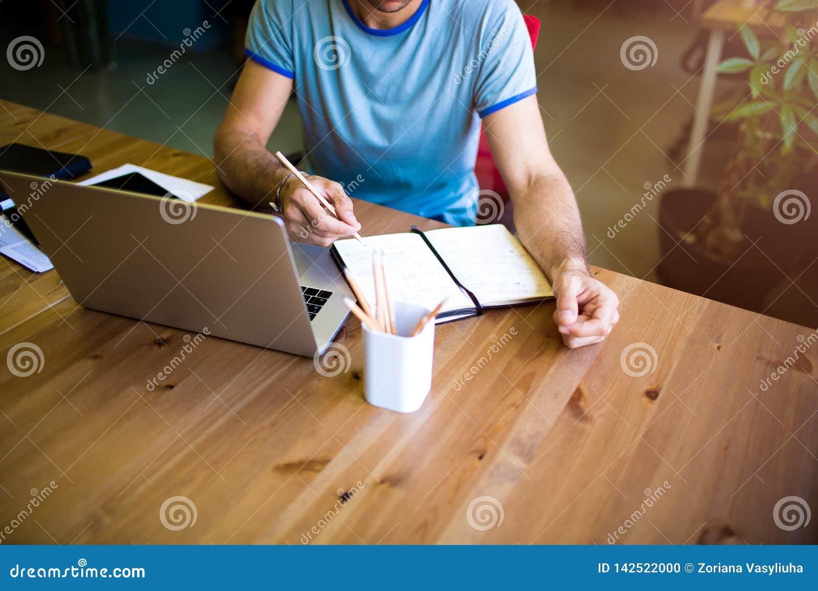Hochschulstudent, der online unter Verwendung des netbook, bereitend zur Prüfung lernt vor Freiberuflerarbeitsabstand