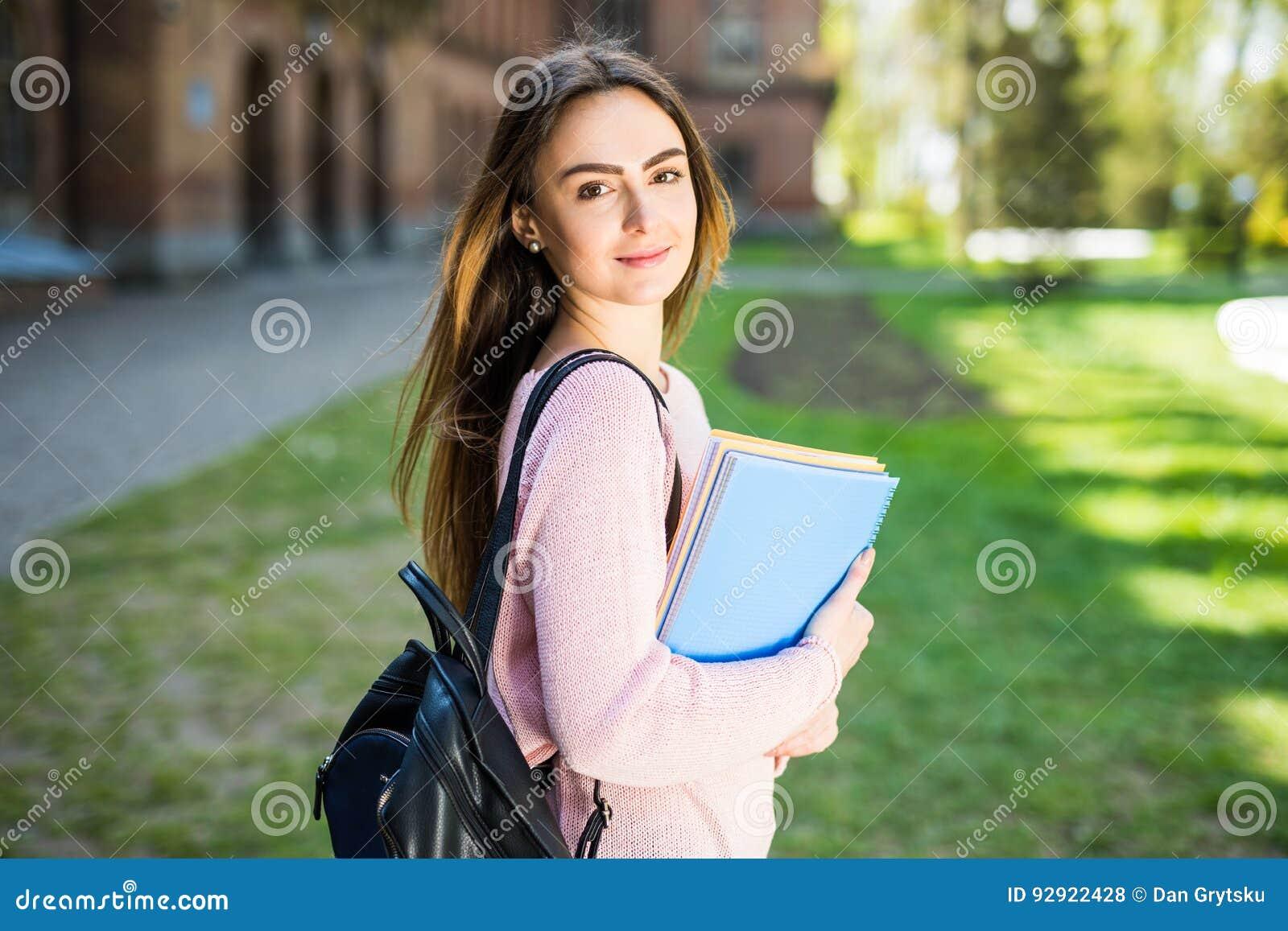 Hochschulstudentmädchen, welches das glückliche Lächeln mit Buch oder Notizbuch im Campuspark schaut