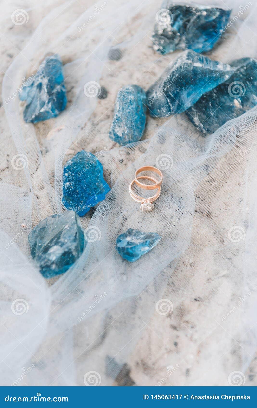 Hochzeit und Verlobungsringe auf einem bloßen Gewebe auf einem Strand mit dekorativen blauen Steinen