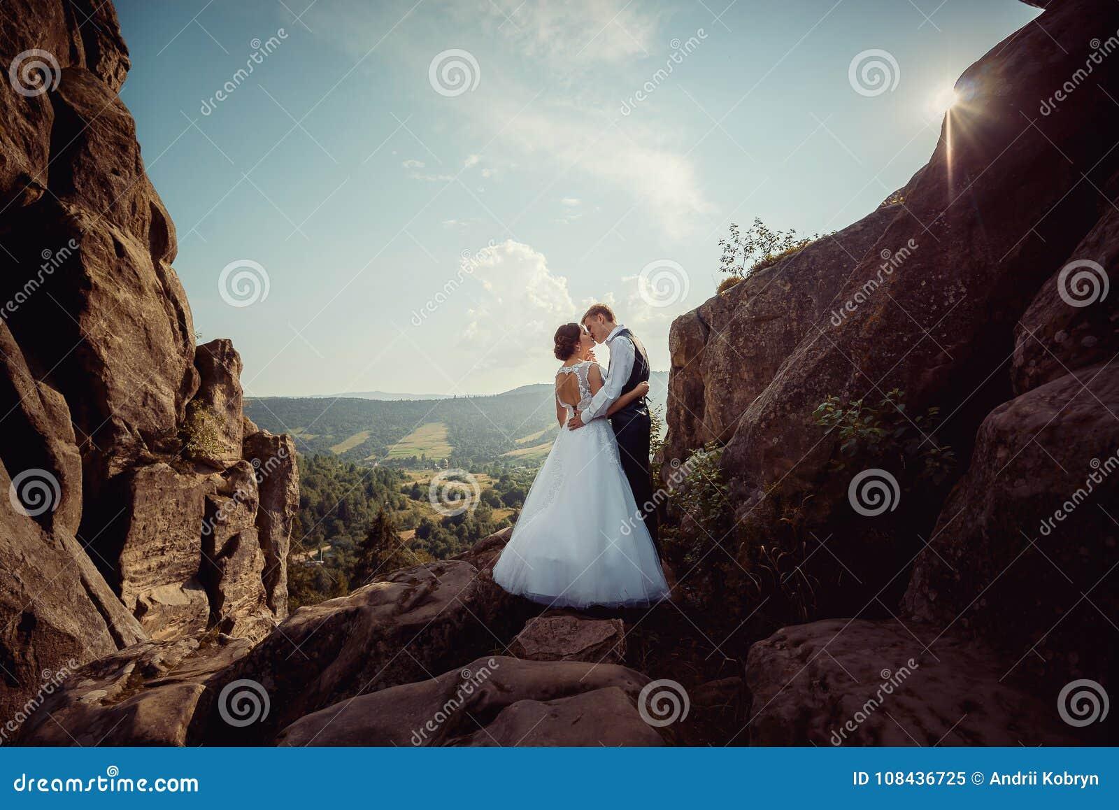 Hochzeit in voller Länge schoss von den stilvollen Jungvermähltenpaaren, die weich auf den Bergen auf den Hintergrund von küssen