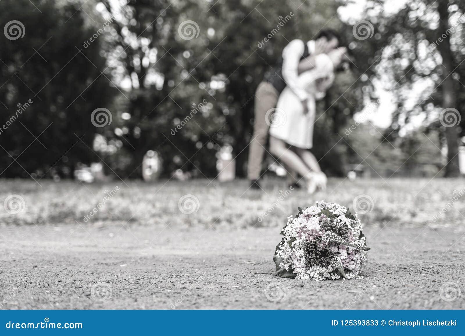 Hochzeitsblumenstrauß vor Jungvermählten verbinden den Hintergrund und küssen flache Tiefe bokeh