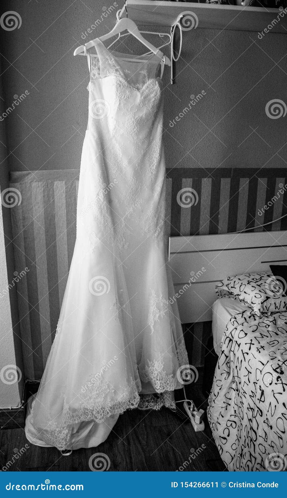 Hochzeitskleid und -bräutigam, die am Fenster sich vorbereiten