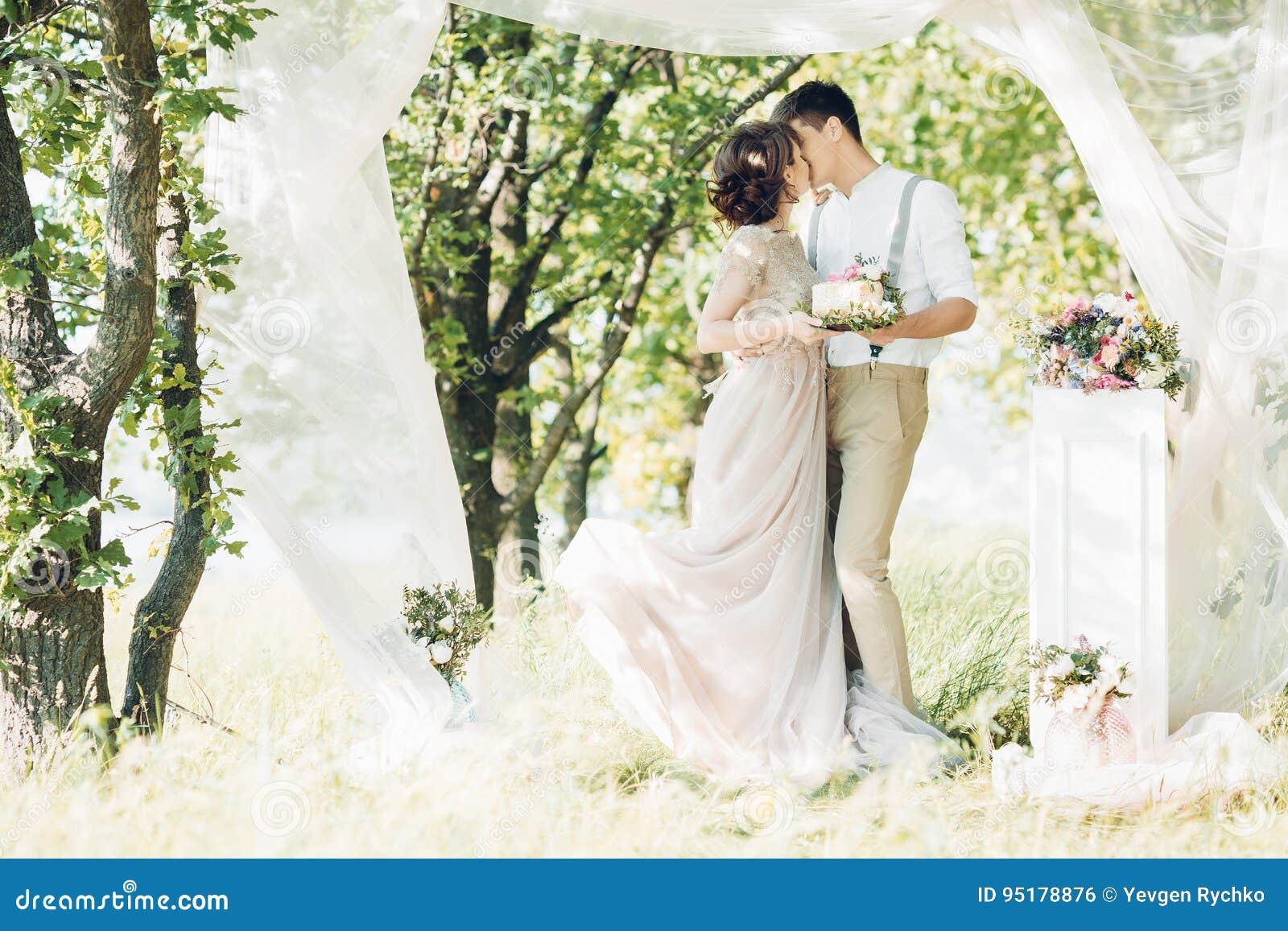 Hochzeitspaare auf Natur Braut und Bräutigam mit Kuchen an der Hochzeit