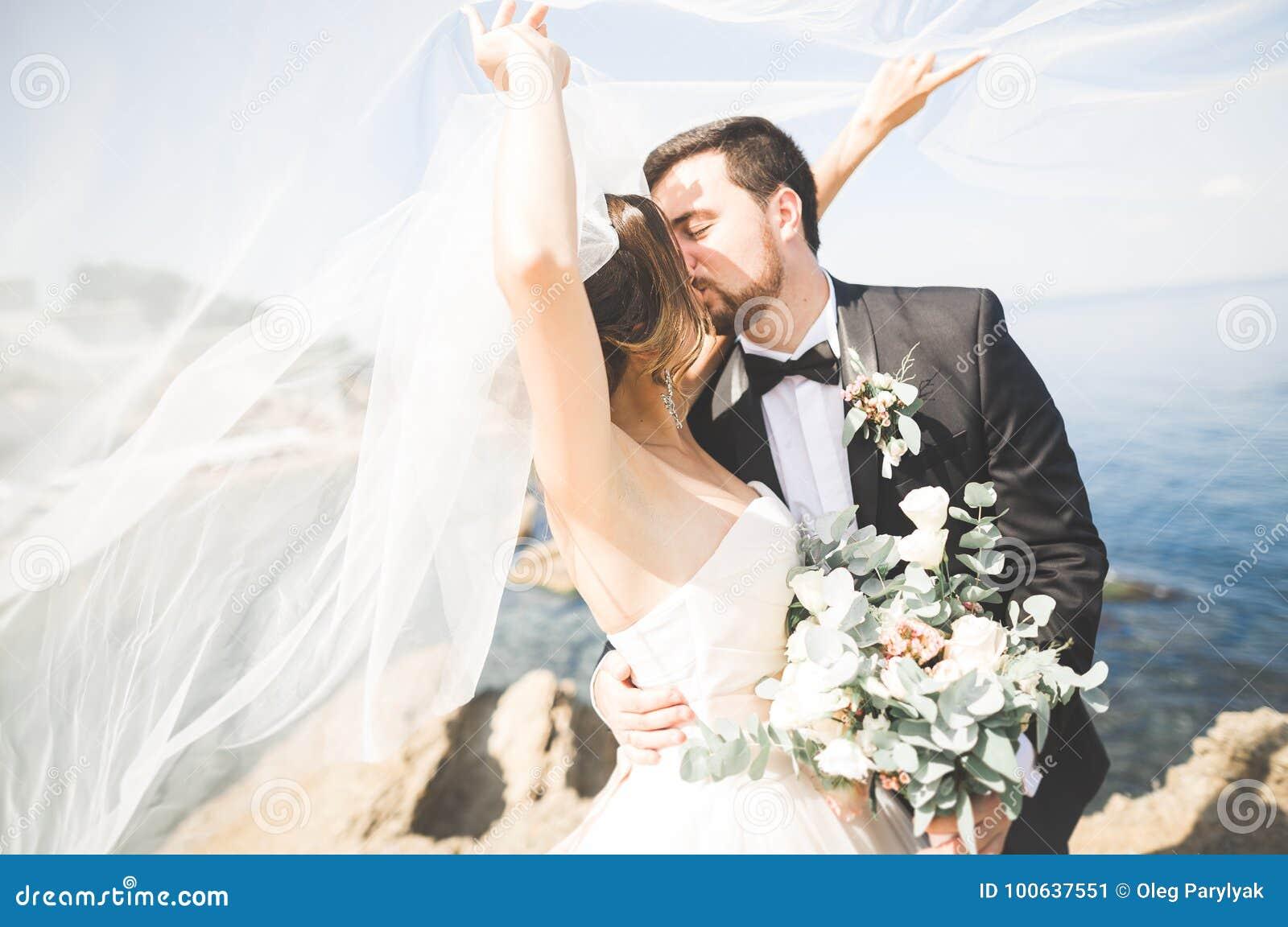 Hochzeitspaare, Bräutigam, Braut mit dem Blumenstrauß, der nahe Meer aufwirft und blauer Himmel