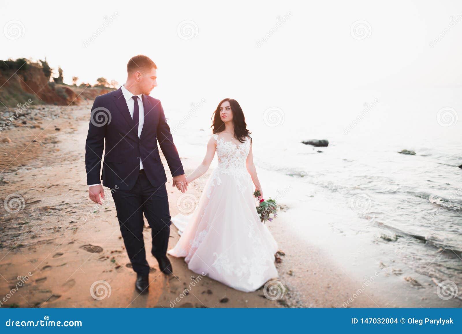Hochzeitspaare, Br?utigam, Braut mit dem Blumenstrau?, der nahe Meer aufwirft und blauer Himmel