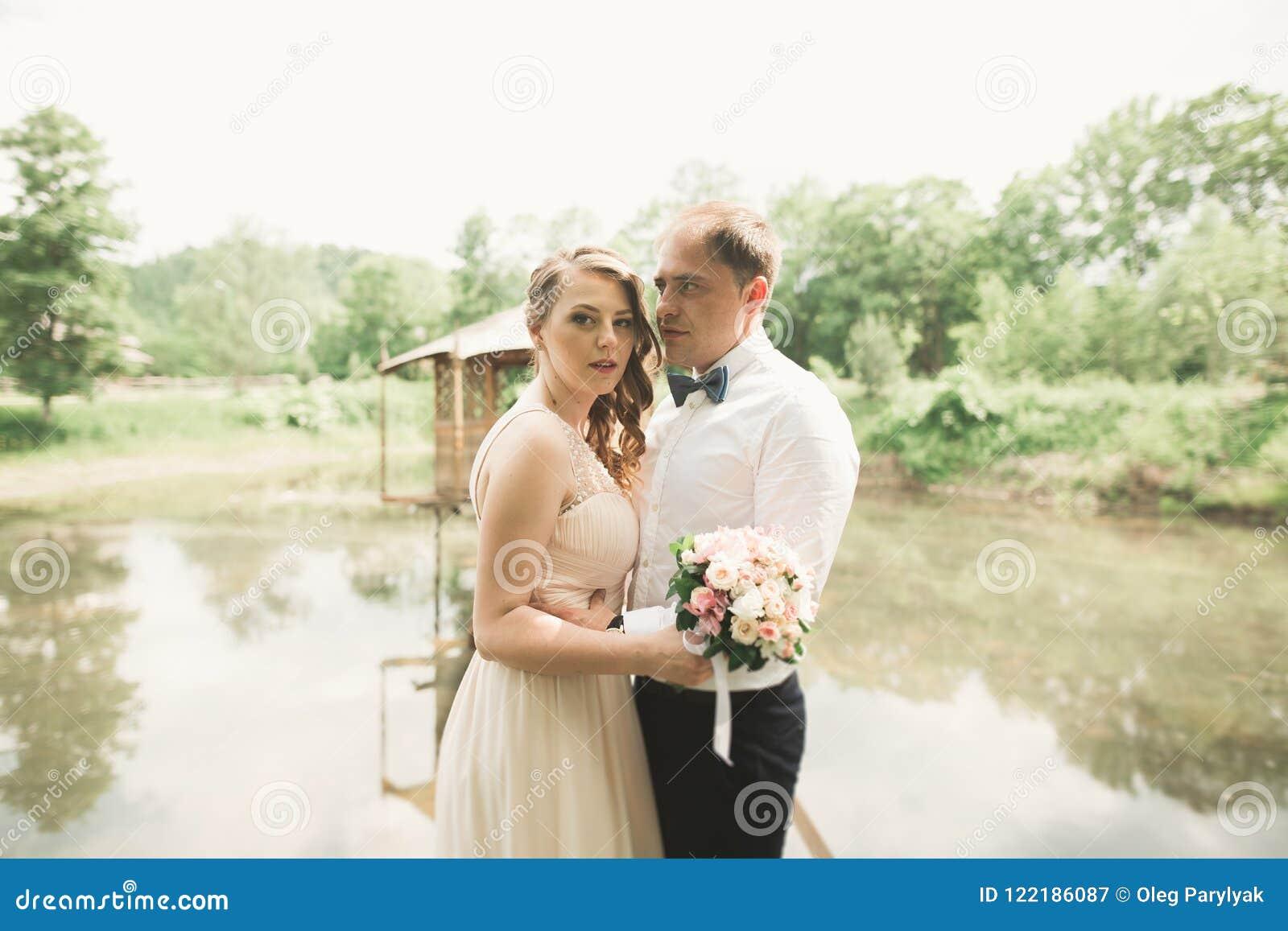 Hochzeitspaare, die an der Brücke umarmen und küssen