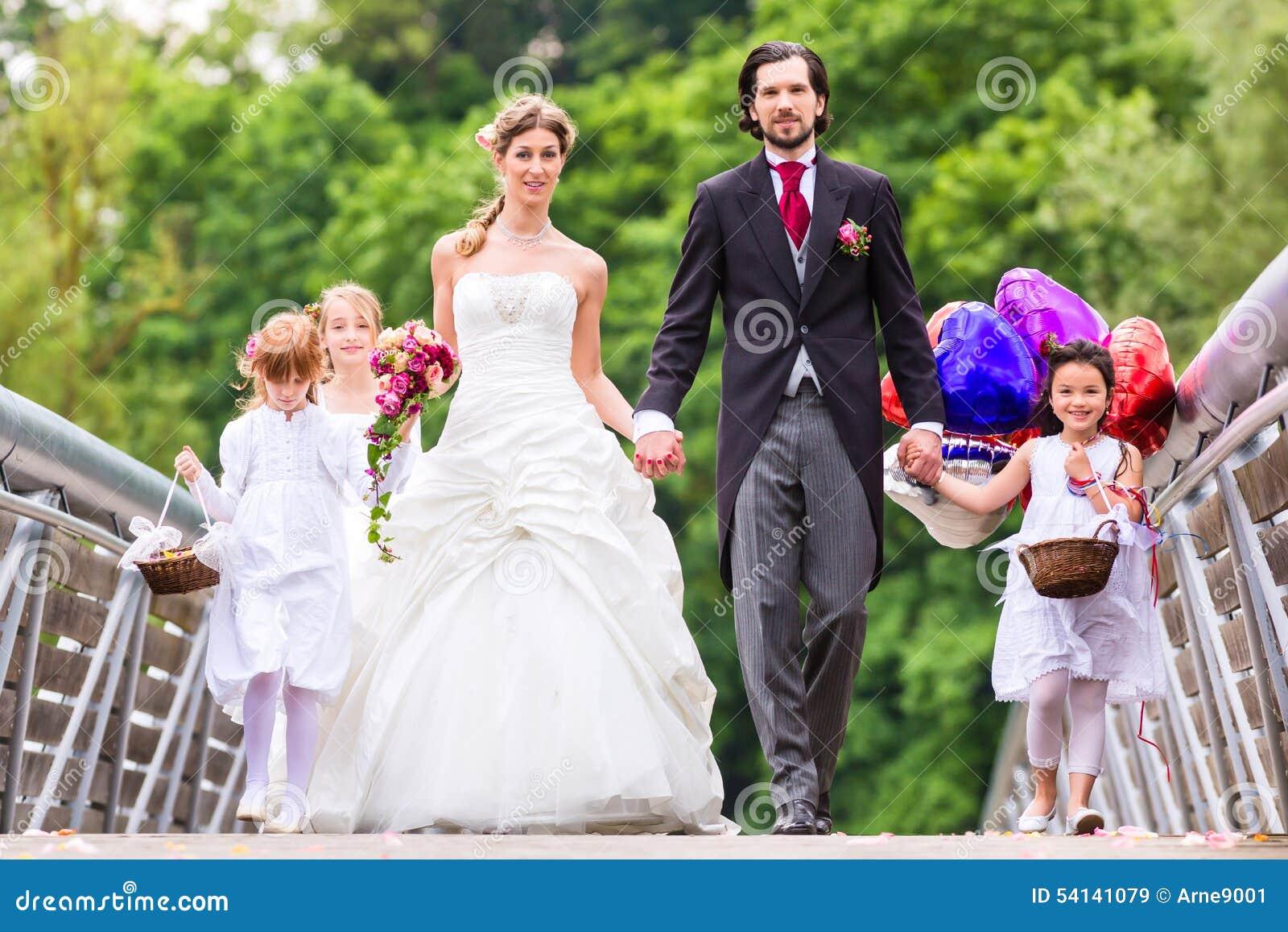 Hochzeitspaare mit Blumenkindern auf Brücke