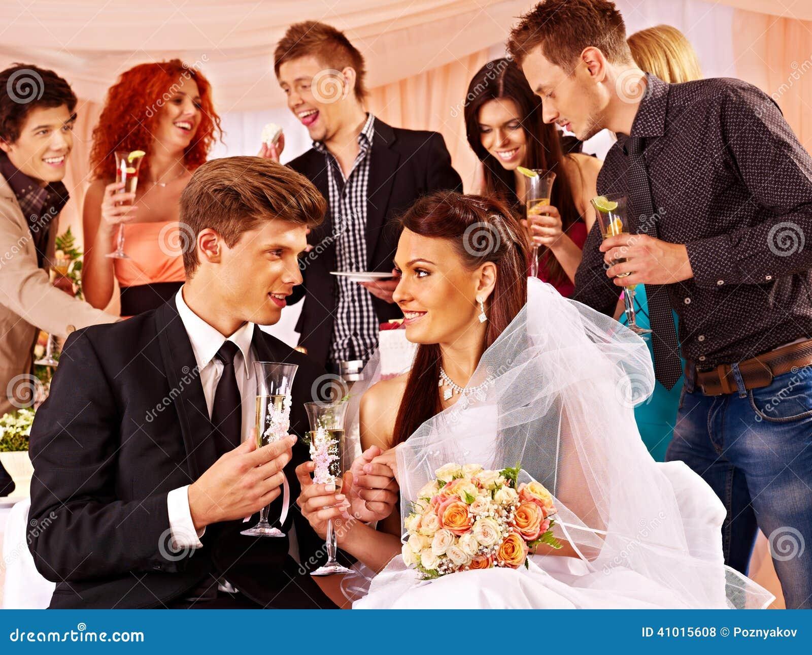 Hochzeitspaare und -gäste, die Champagner trinken