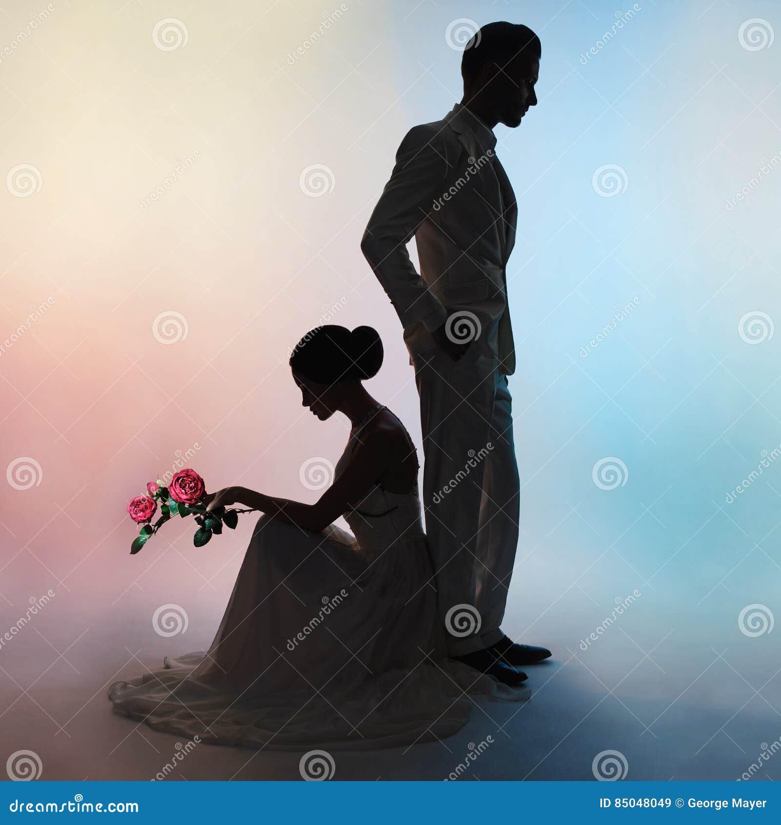 Hochzeitspaarschattenbildbräutigam und -braut auf Farbhintergrund