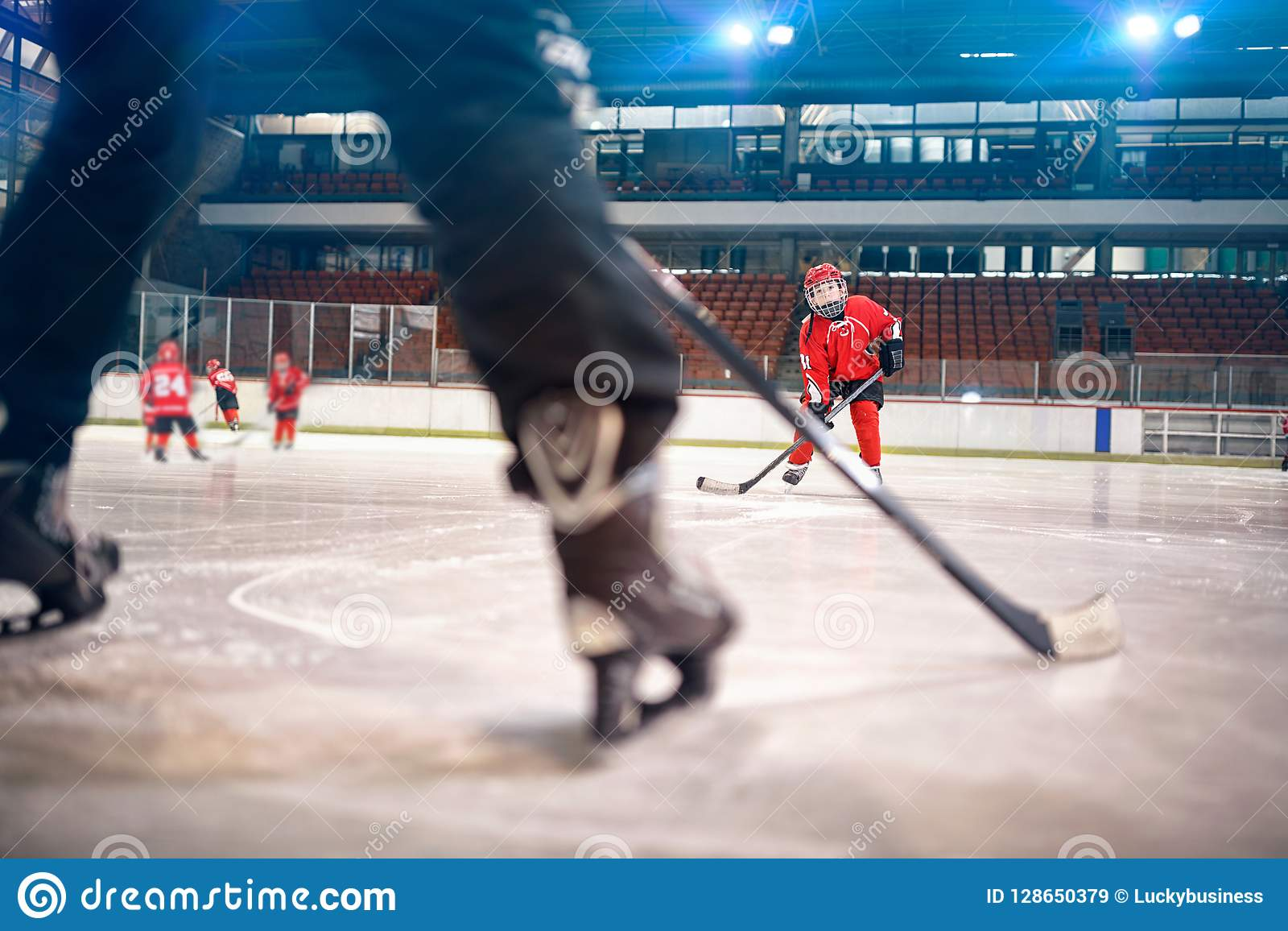 Hockey match at rink boy player in action